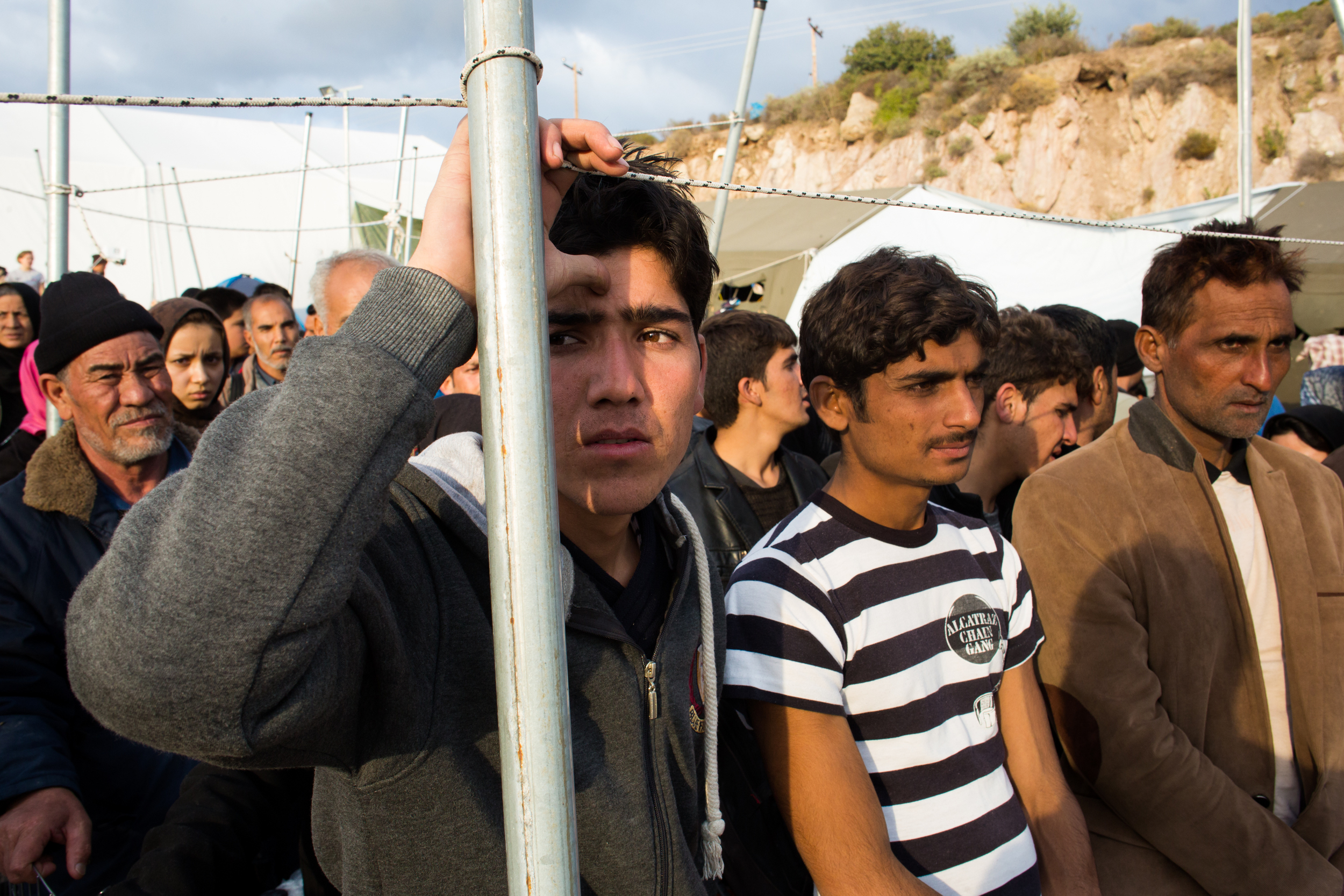 A group of men wait to board a bus bound for the registration camp at the southern end of the island of Lesvos. Families are given priority when loading buses bound for the registration centers at the south of the island and young men are often asked to sleep outside until more buses arrive the next morning.