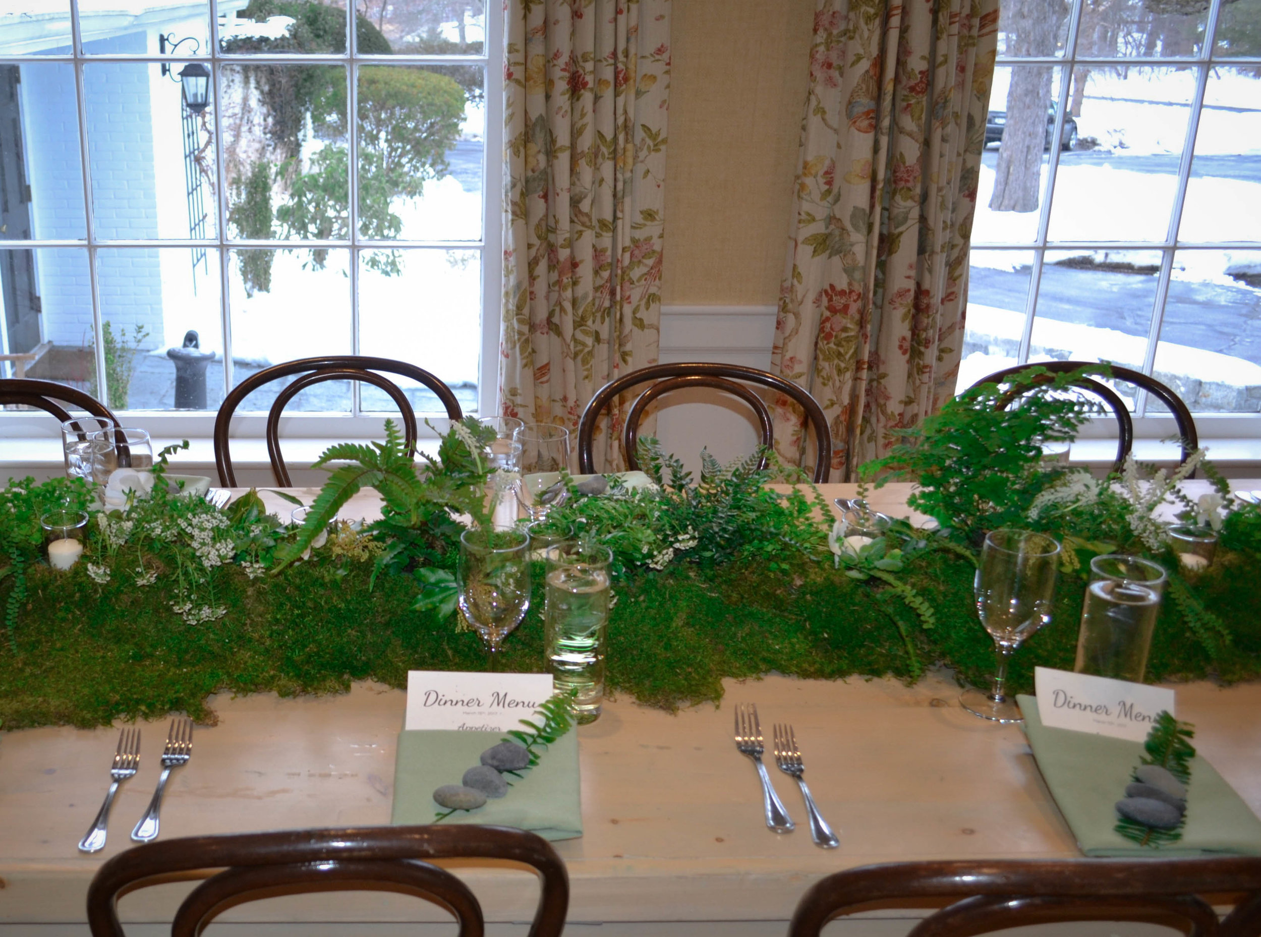Lush 6' moss table runners were created and topped with votives,several fern varieties, clover, foraged andromeda and seasonal white flowers such as muscari, alyssum and pansies