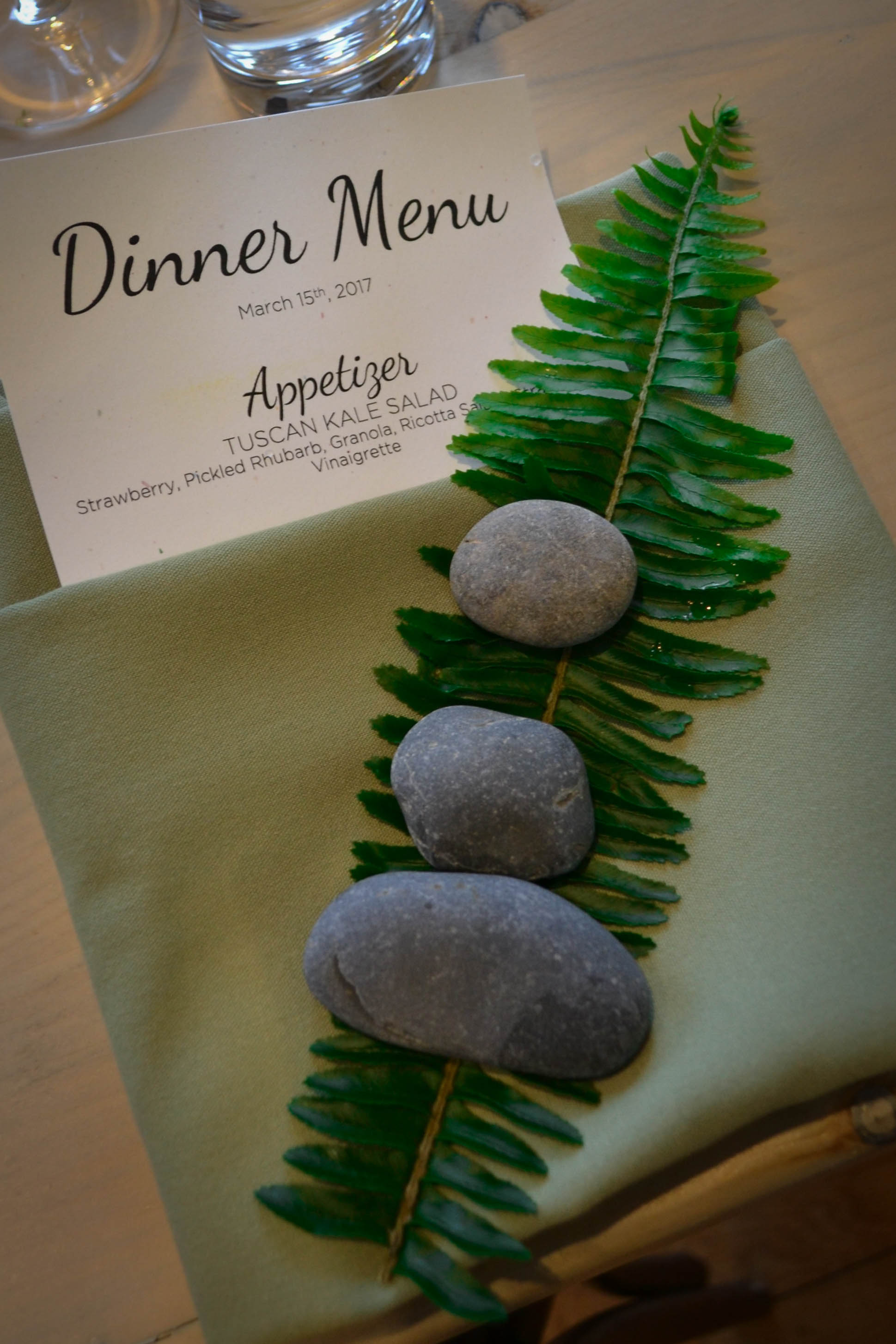 Three meditation stones and a single fern sprig were placed at each table setting.