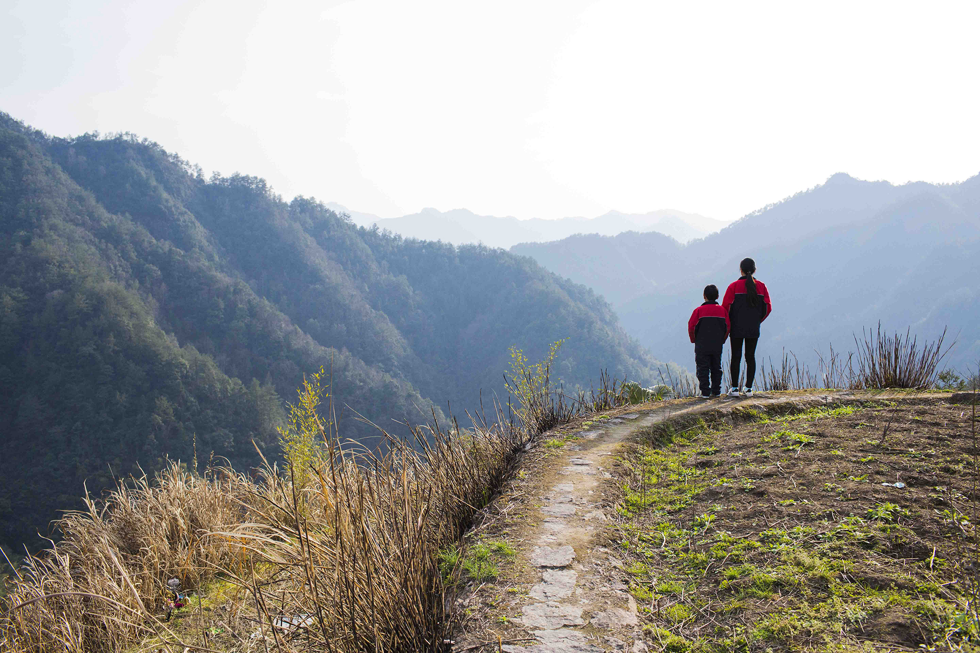 "Jinhao Ma and Leting Ma take a stroll before dinner outside their grandmother's house in the Mashang Mount area of Wenzhou, China, on March 25, 2016. Their big sister, Meiting Ma, is away at high school. The Ma children are among China's ""left-behind"" kids. Their parents are in Shanghai, 250 miles away from Mashang Mountain, working in a breakfast shop to make more money to raise them."