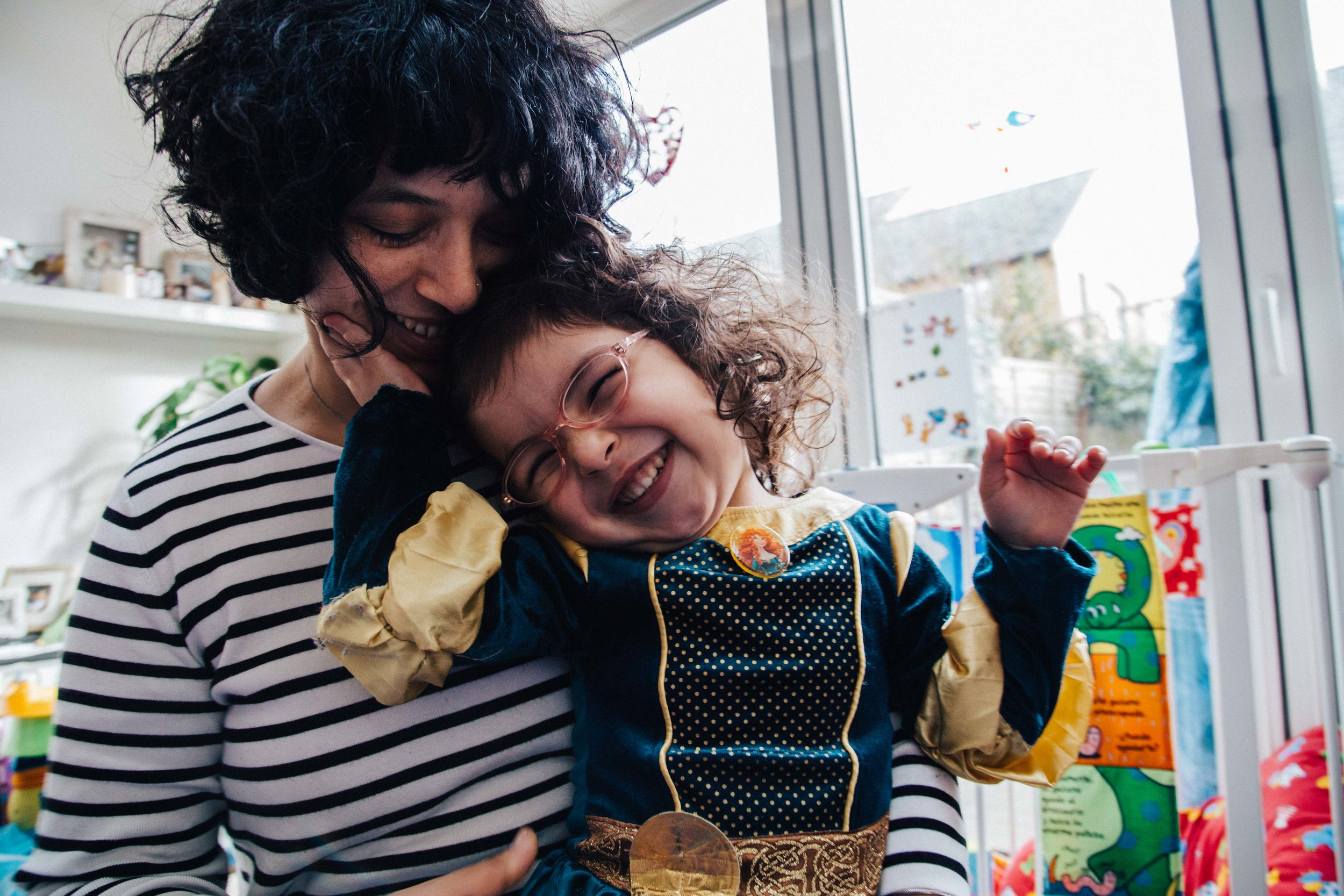 Mum holding little girl and smiling during family photo session in London