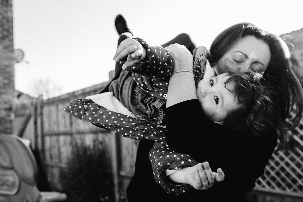 Mum holding and kissing daughter