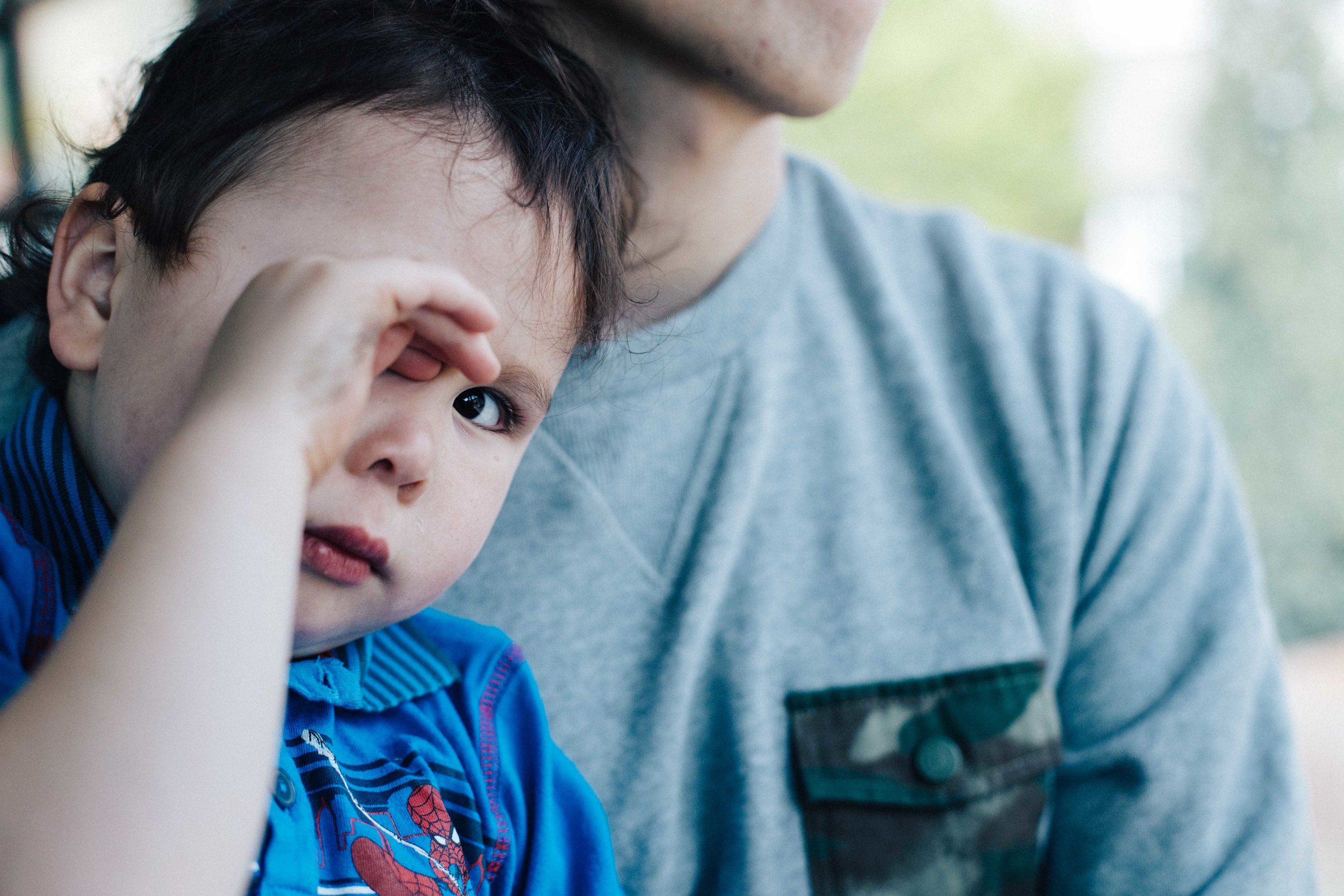 Boy rubbing his eyes on father's lap - children photography London