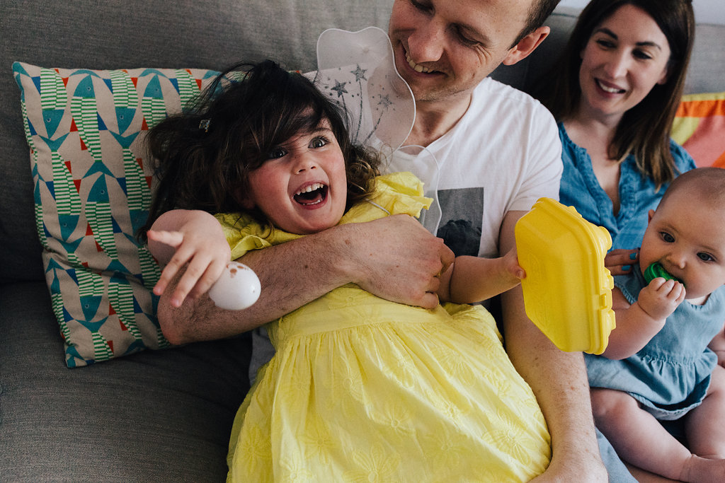 Family laughing together on the sofa during a family photo session by Marion & You Photography