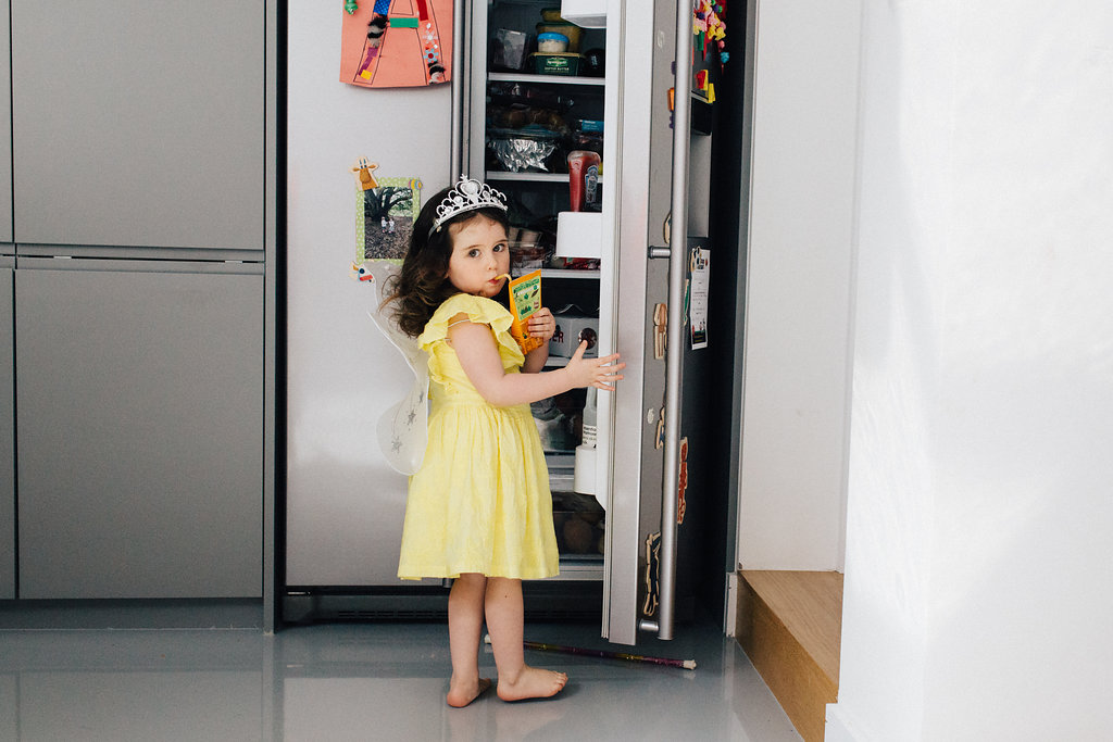 Little girl dressed as a princess opening the fridge during family photo session in Beckenham, Kent, by Marion & You Photography