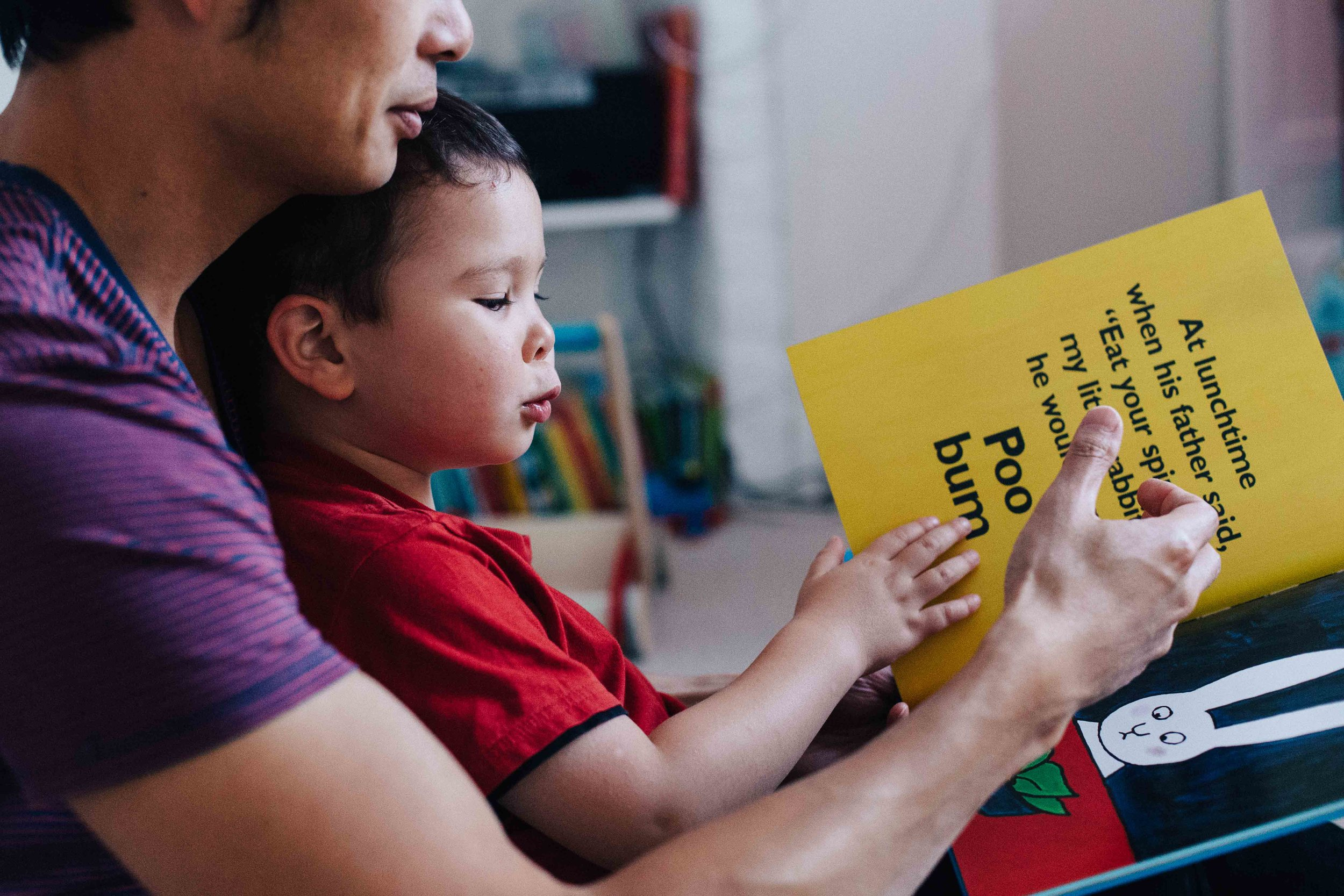 Child reading Poo Bum book with his father