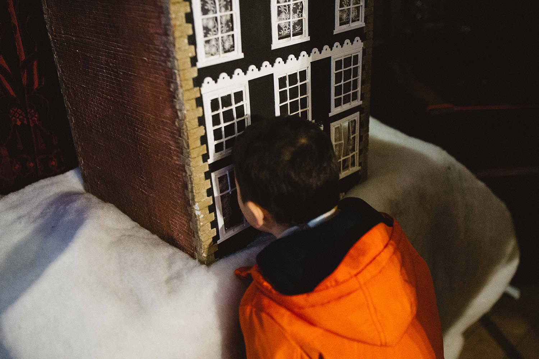 Boy looking through doll house