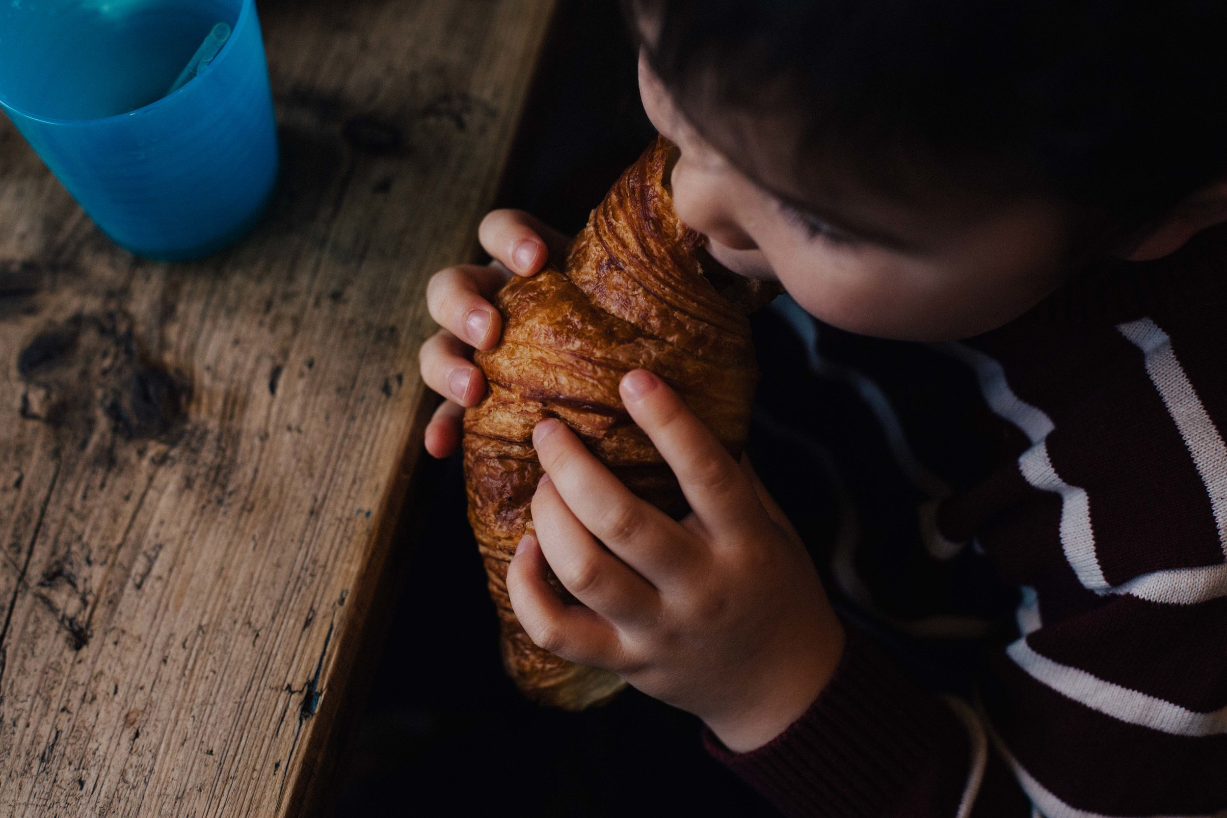 Boy eating a croissant