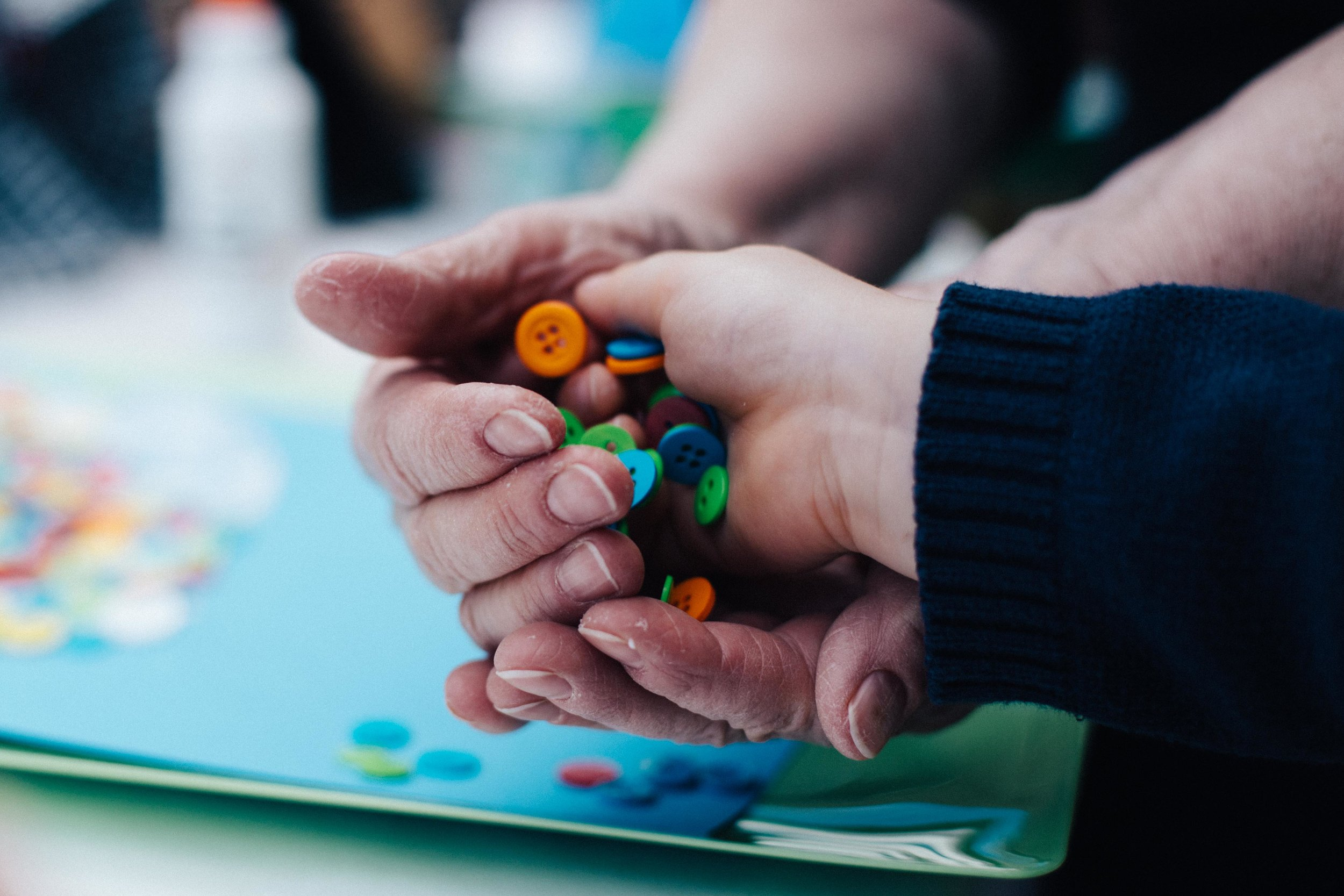 Child and grandmother hands with buttons