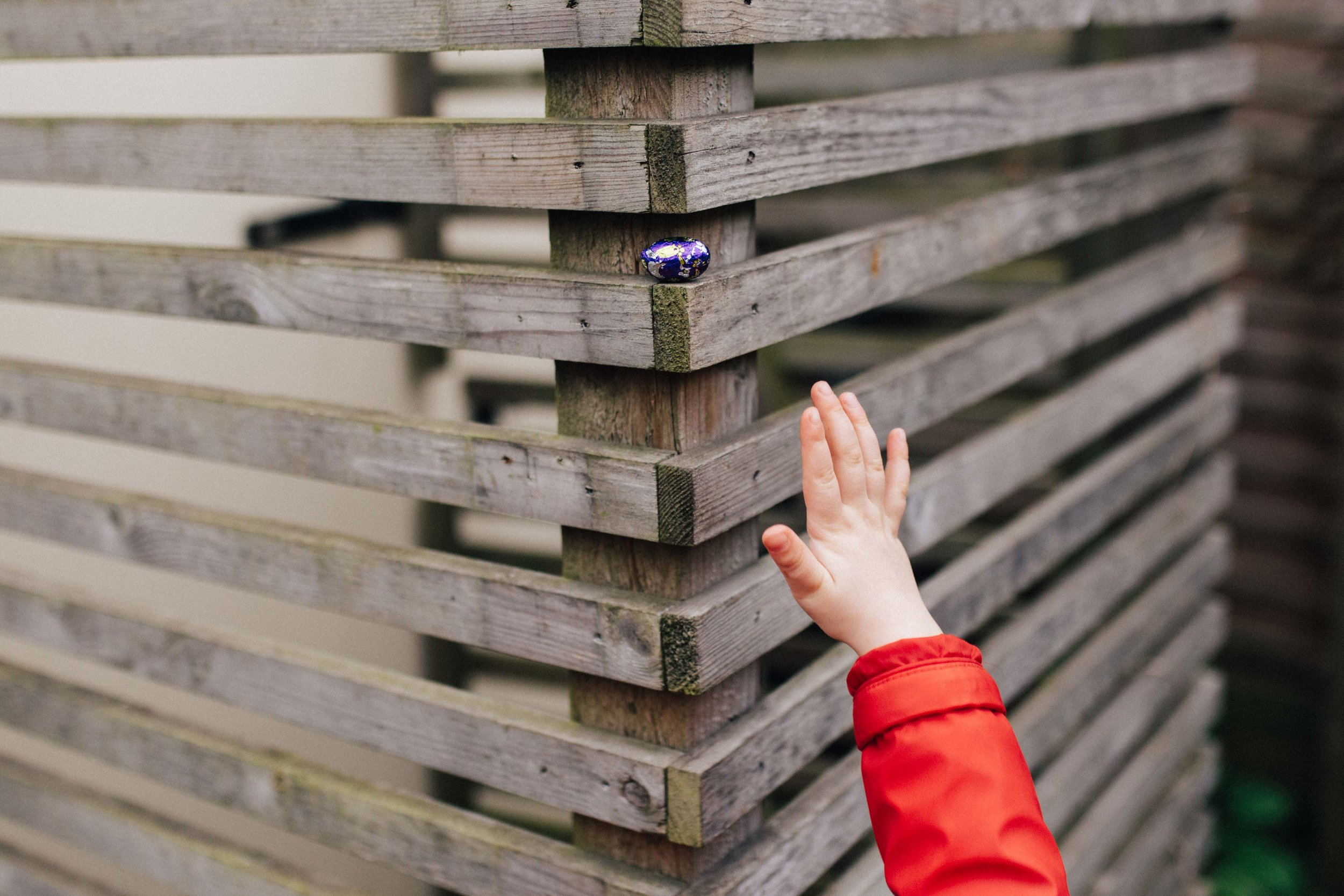 Child hand trying to reach an Easter egg