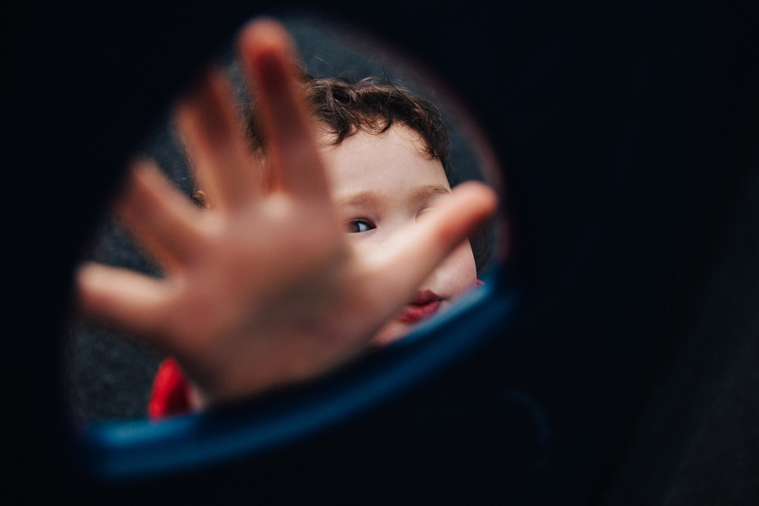 Child's hand hiding his face
