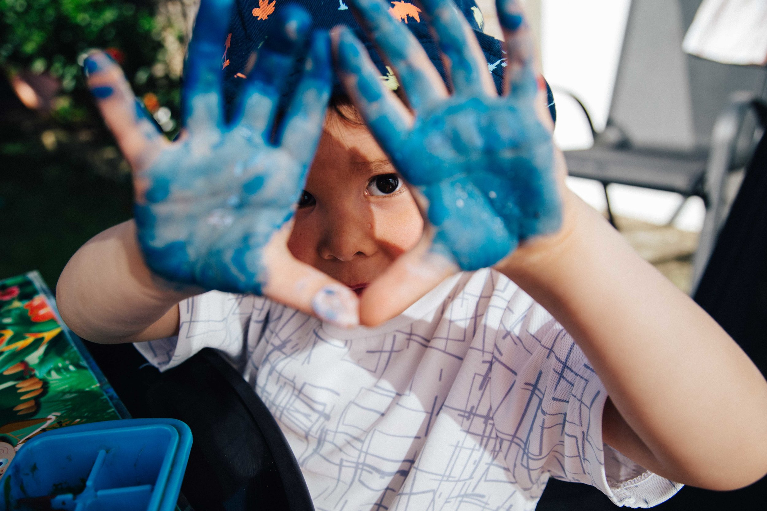 Boy with hands full of blue paint