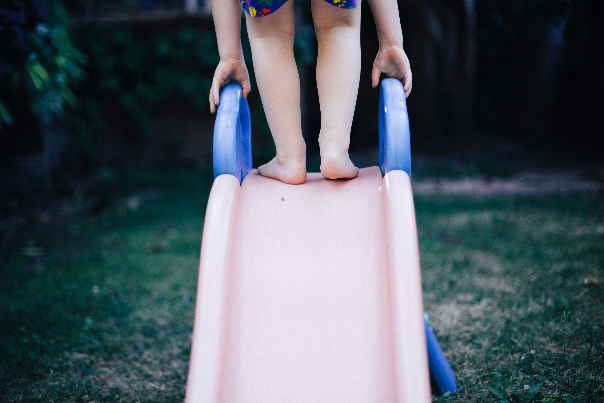 Child's feet at the top of a slide