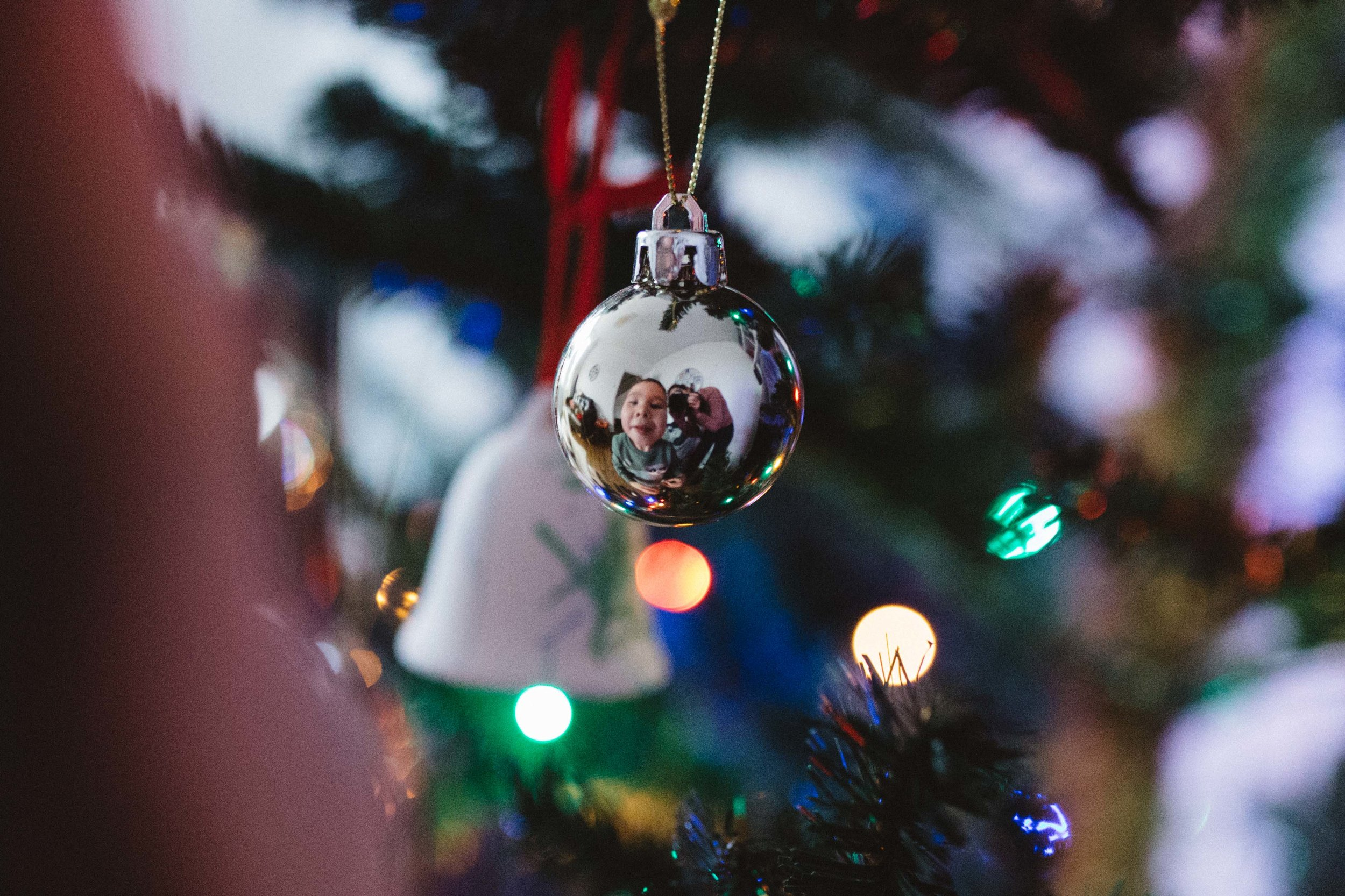 Reflection of boy in Christmas baubble