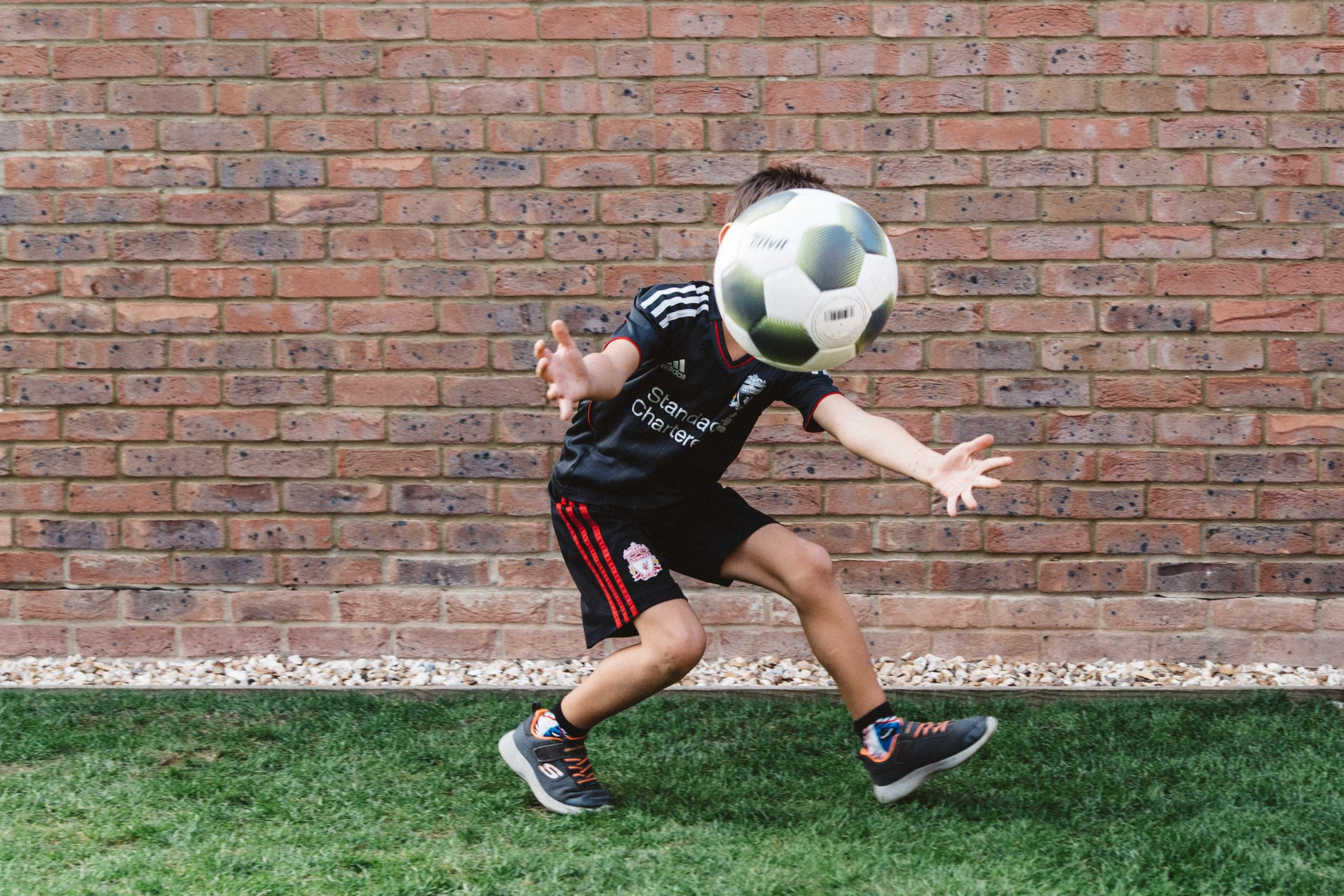 Foot ball in front of boy' face