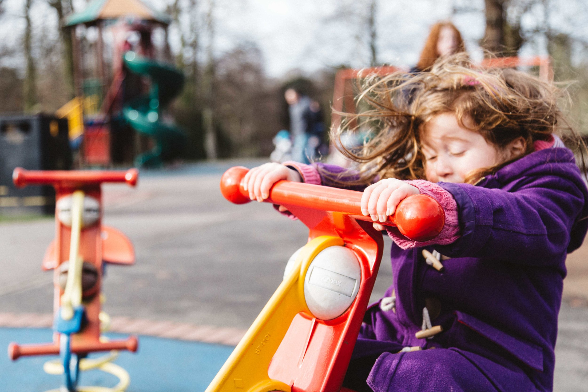 Little girl playing in Kelsey Park playground during family photoshoot in Beckenham