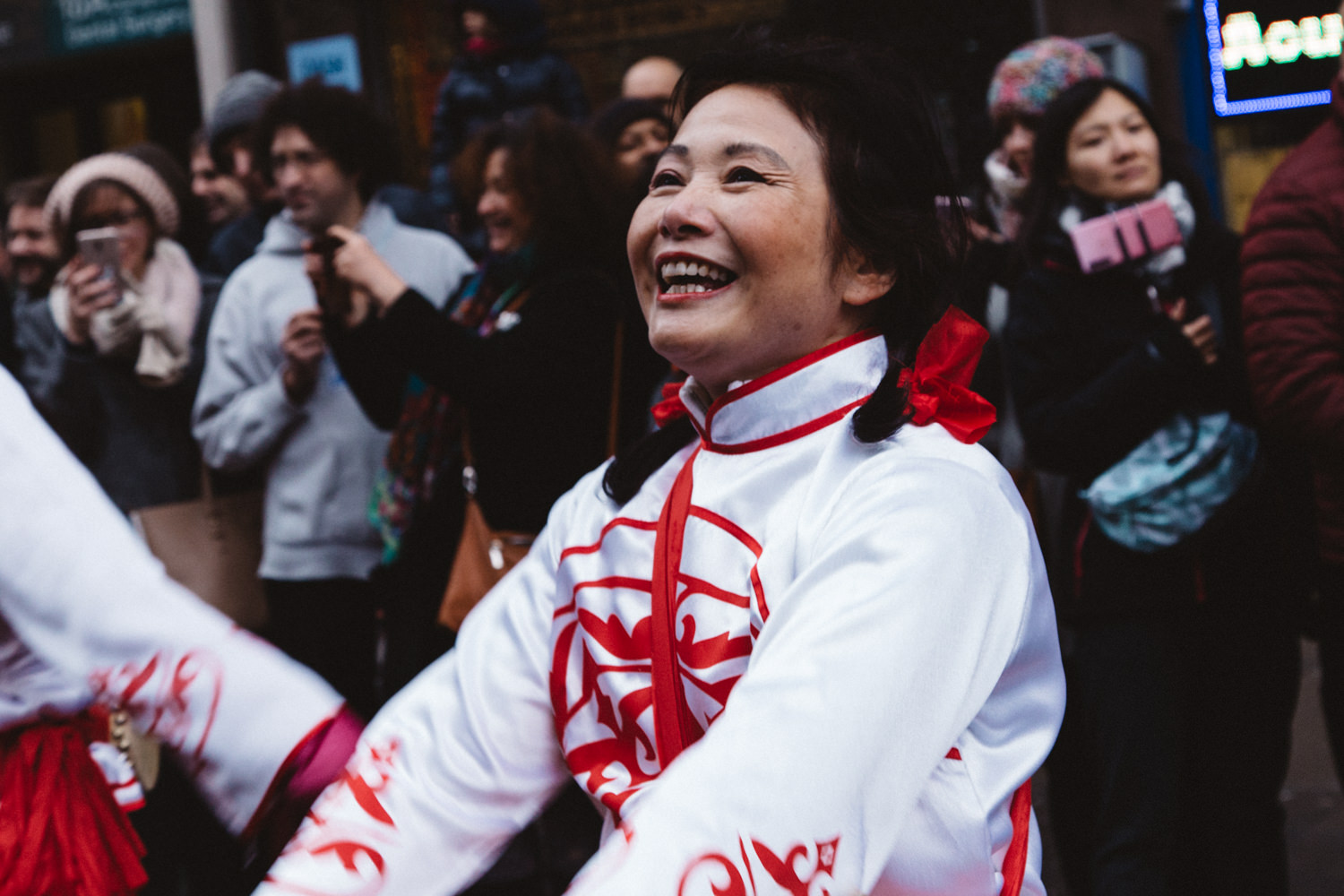 Chinese woman dancing and smiling during the Chinese New Year Parade in London