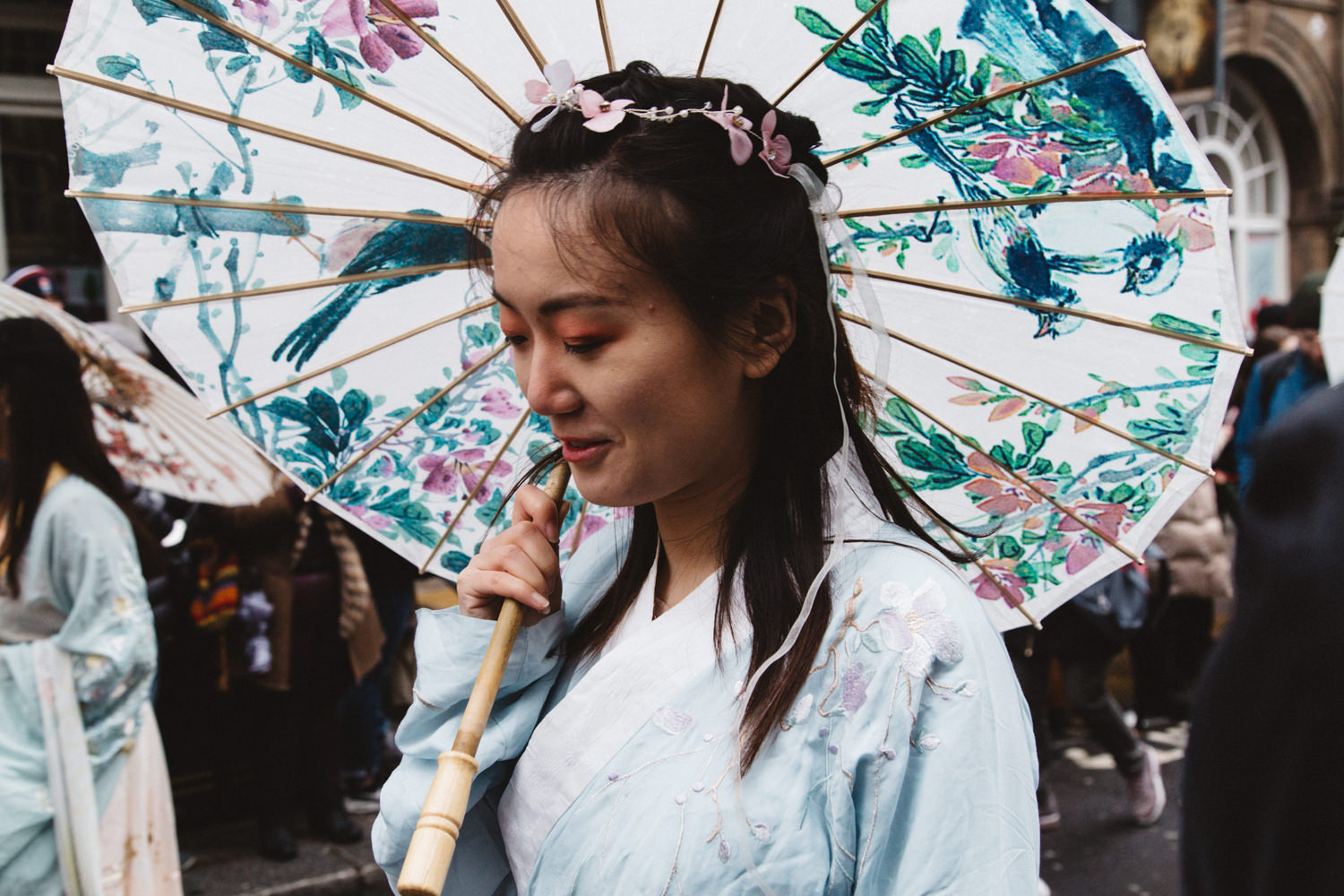 Chinese woman holding an umbrella with flower decorations during the Chinese New Year Parade in London
