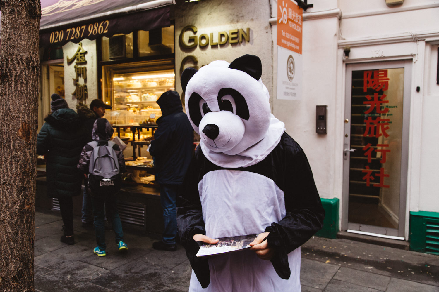 Person dressed as a panda in front of cake shop during the Chinese New Year celebrations in London