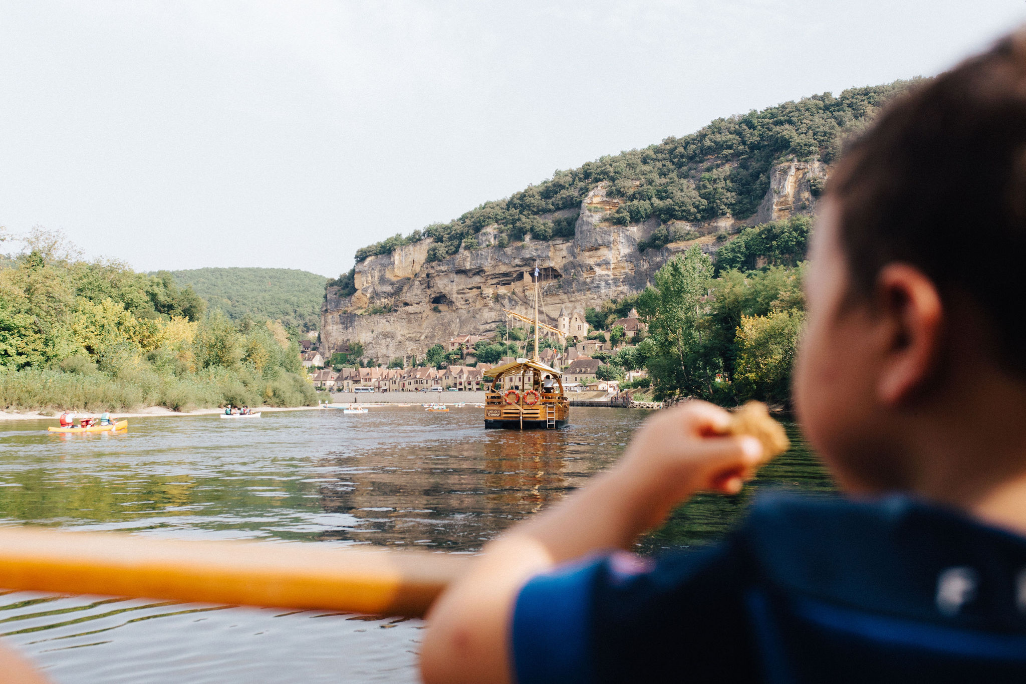 Boy looking at La Roque Gageac village from a gabarre boat
