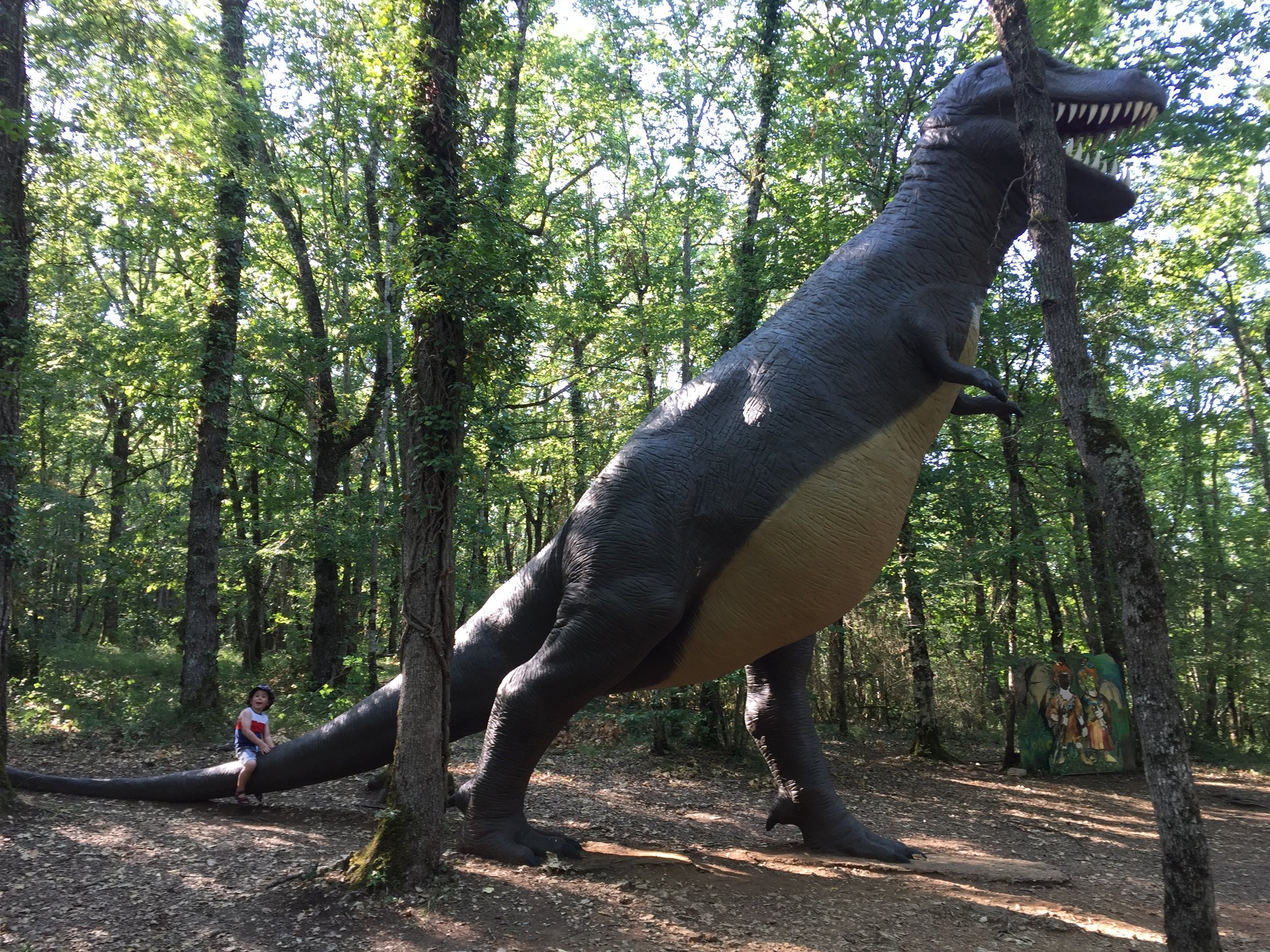Real-size dinosaur with child on tail at The Conquil, Dordogne, France