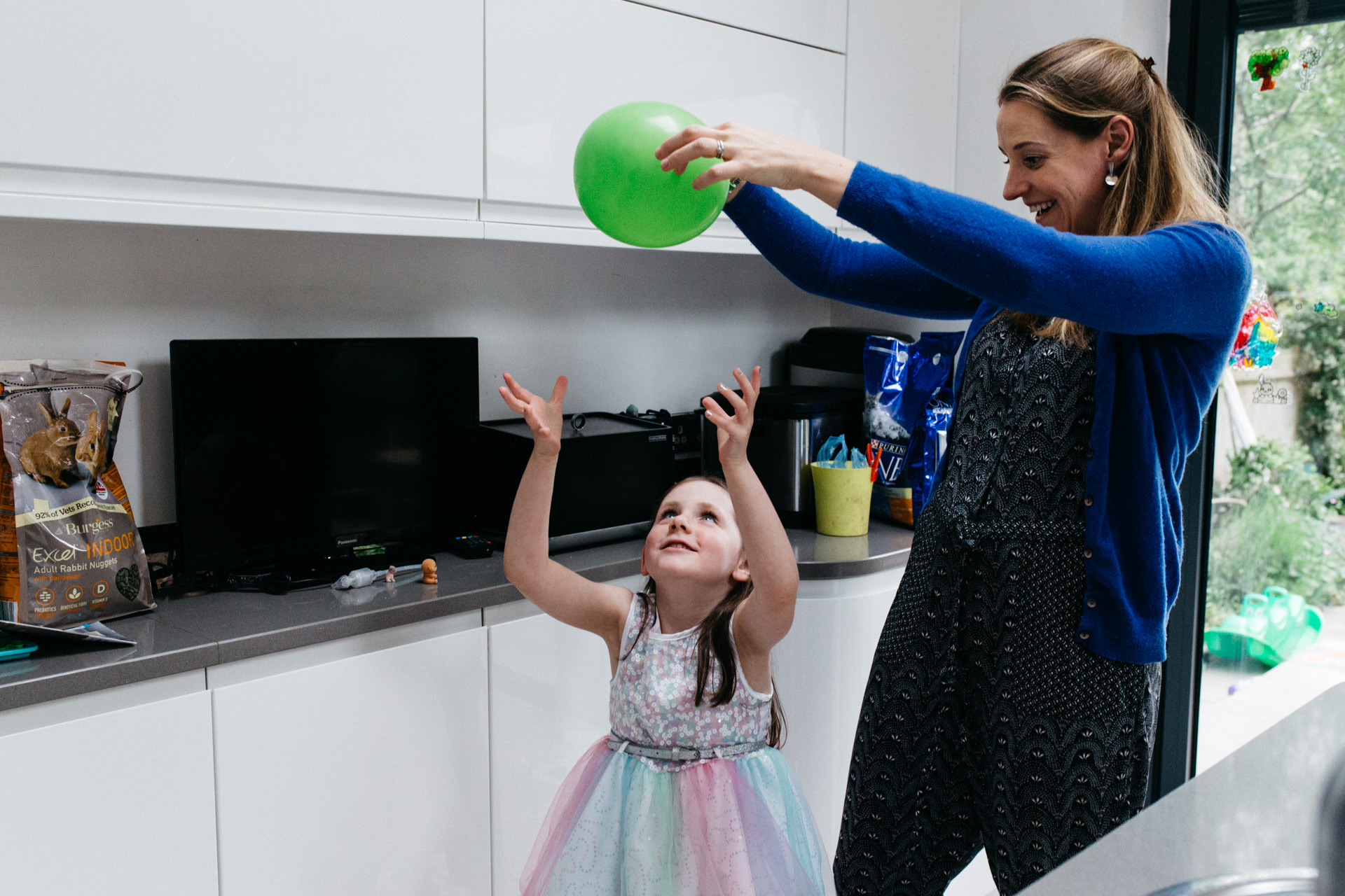 Mother and daughter playing with balloon during family photoshoot