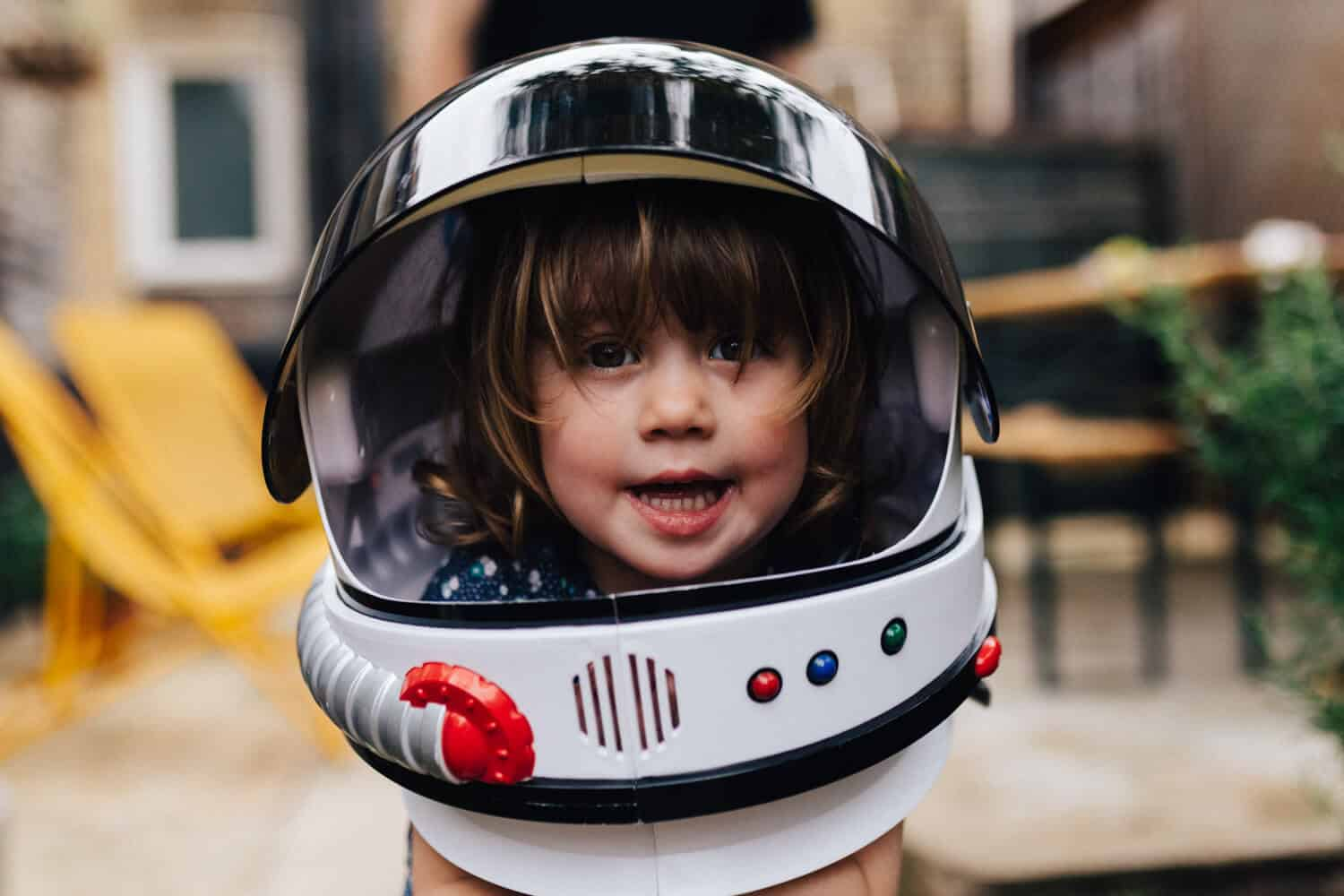Toddler girl smiling wearing space helmet