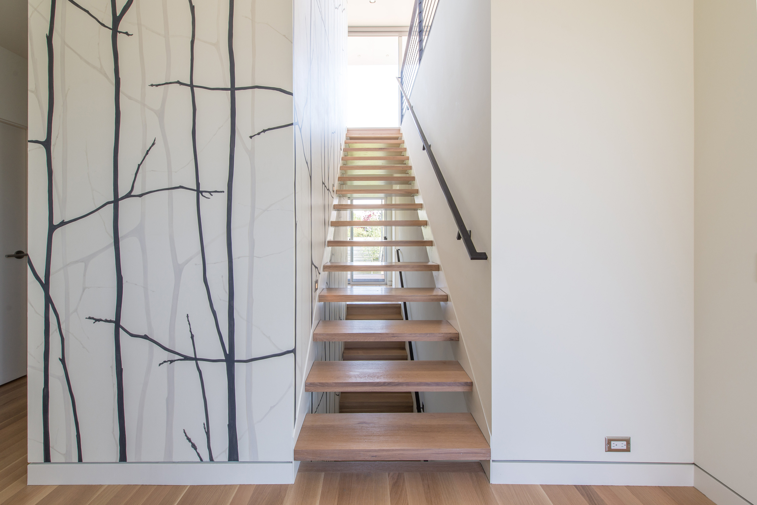 Entry on the second floor. The image continues below these stairs to the basement and above through the kitchen to the top of the rooftop staircase.Photo by Andrew van Leeuwen, BUILD LLC