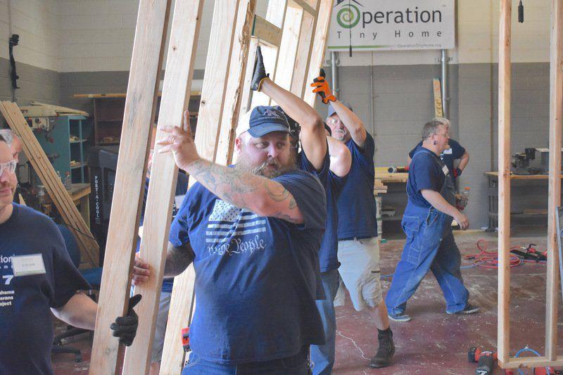 Garrett Quinn, a Navy veteran, helps move a section of a tiny house.