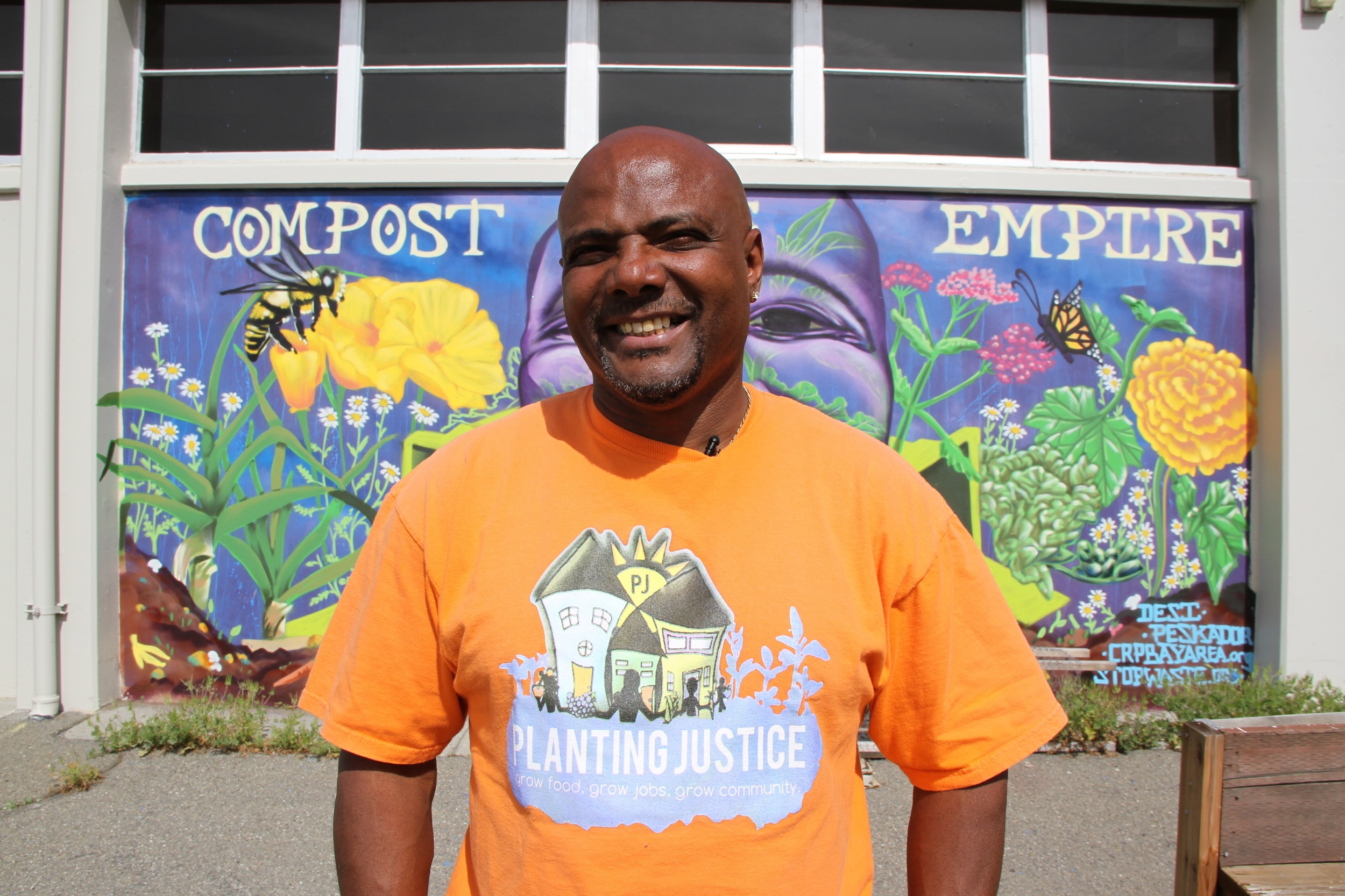 Anthony Forrest, Planting Justice's first re-entry hire, stands in the garden he built at McClymond's High School in West Oakland, where he now teaches kids about healthy eating every week.