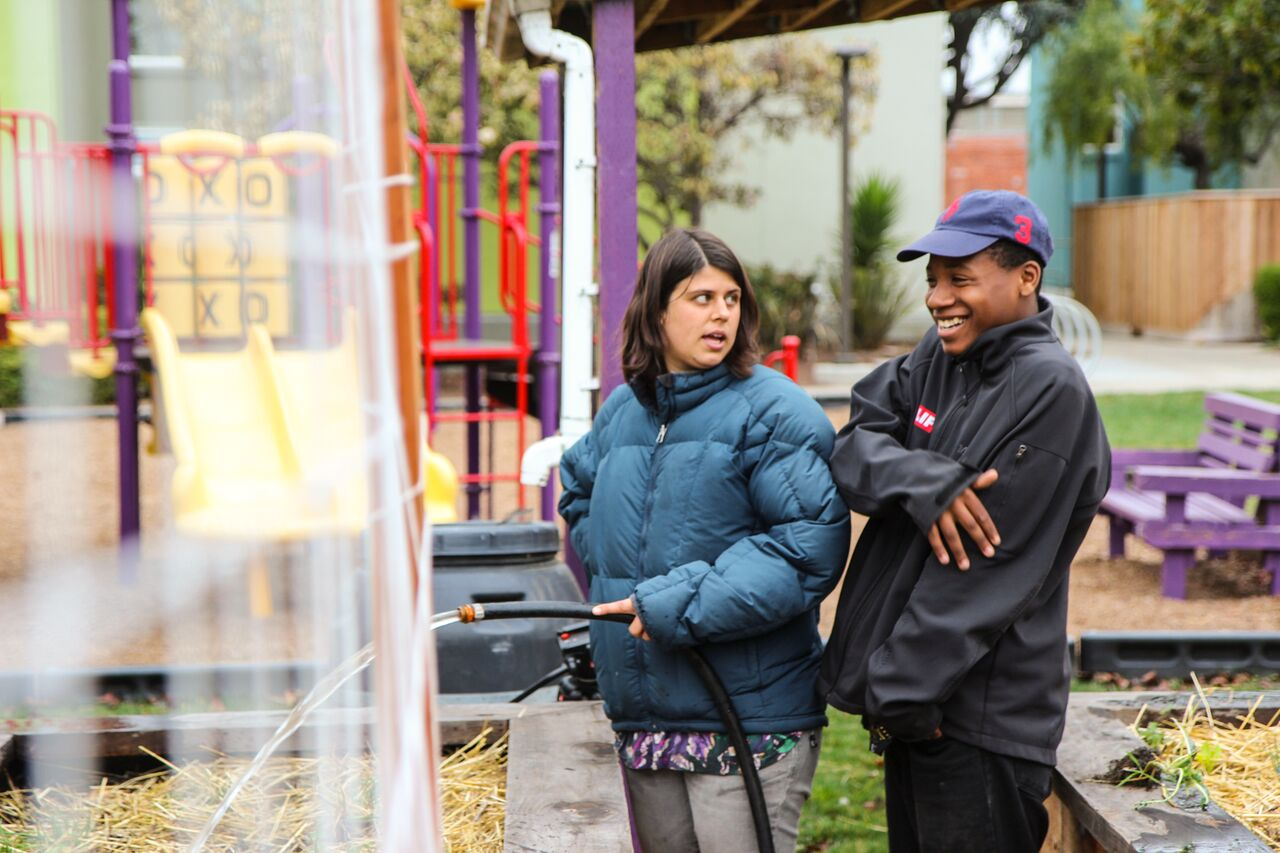 Haleh waters one of Planting Justice's urban gardens with Tylen, a member of the organization's Education team.