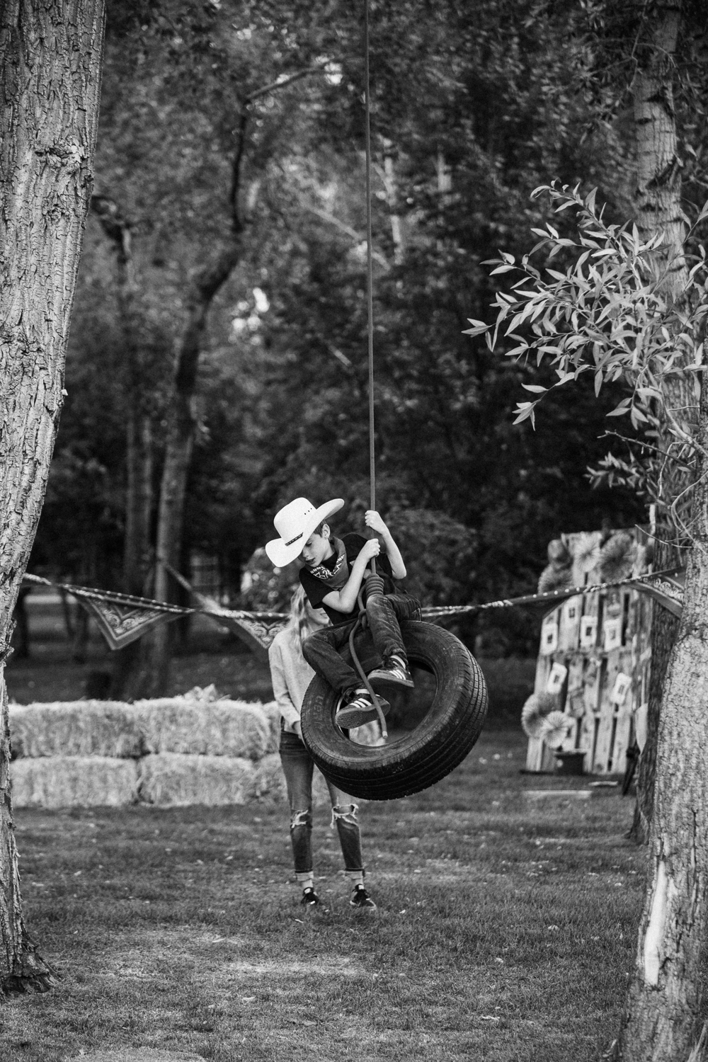 black-and-white-boy-on-tire-swing-in-cowboy-hat-at-legacy-days-in-heber-utah