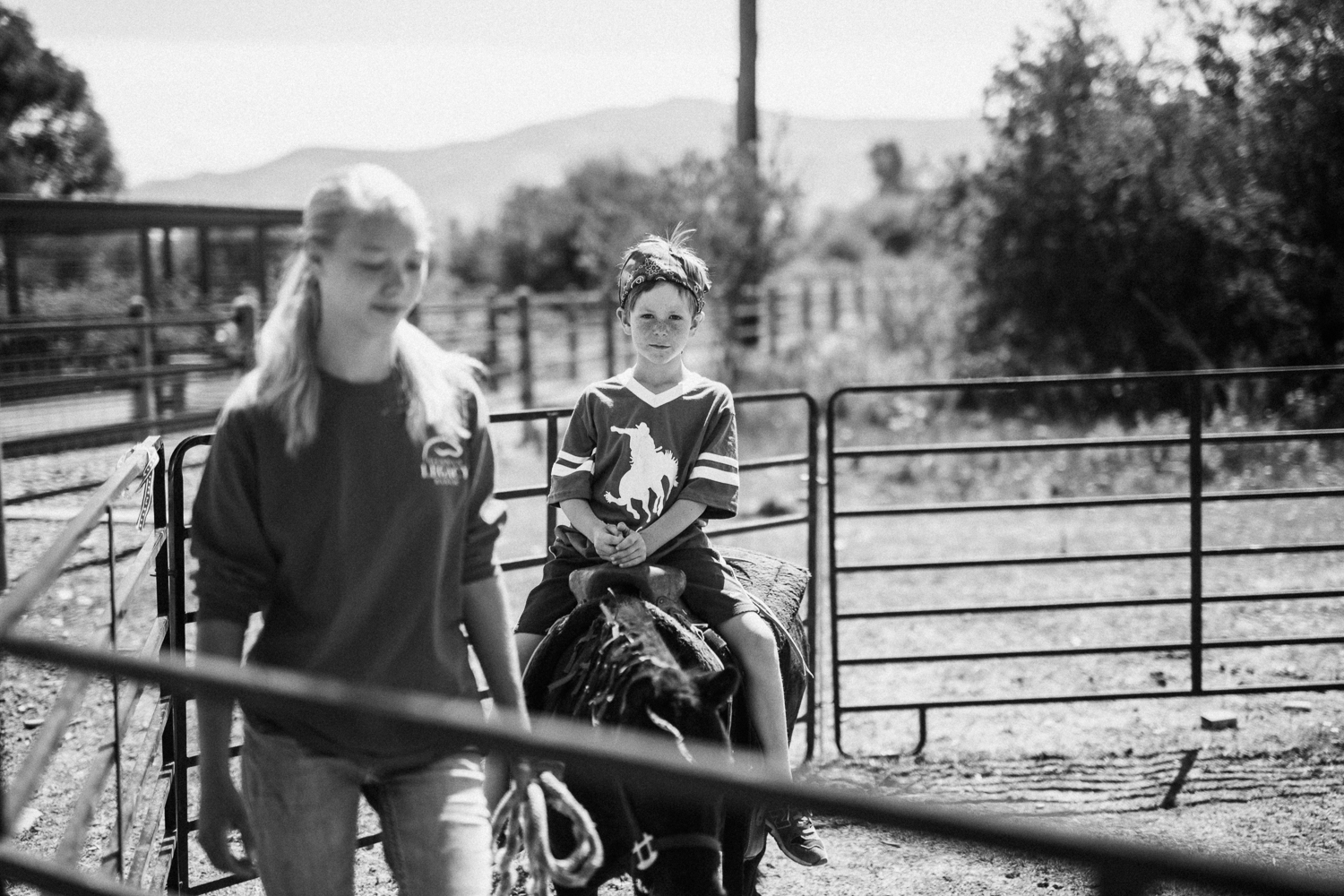 black-and-white-portrait-of-boy-riding-miniature-pony-at-legacy-ranch-heber-utah