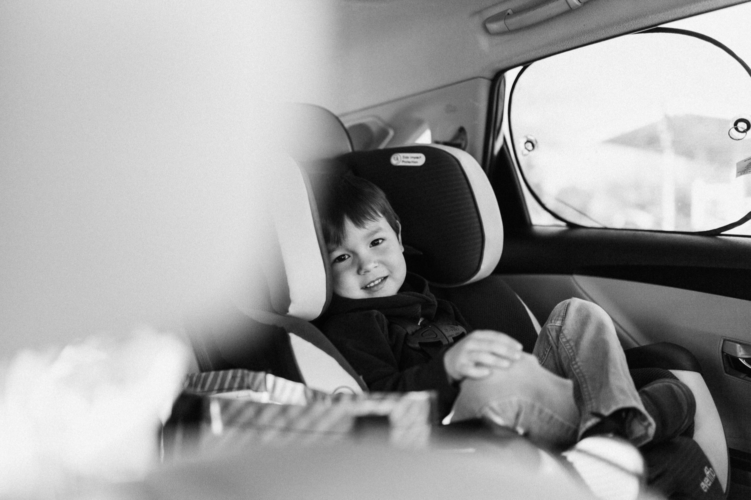 black and white lifestyle image of boy in carseat san diego california
