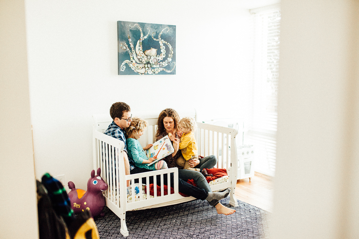 family-reading-book-on-bed-at-home-lifestyle-photography-slc-utah