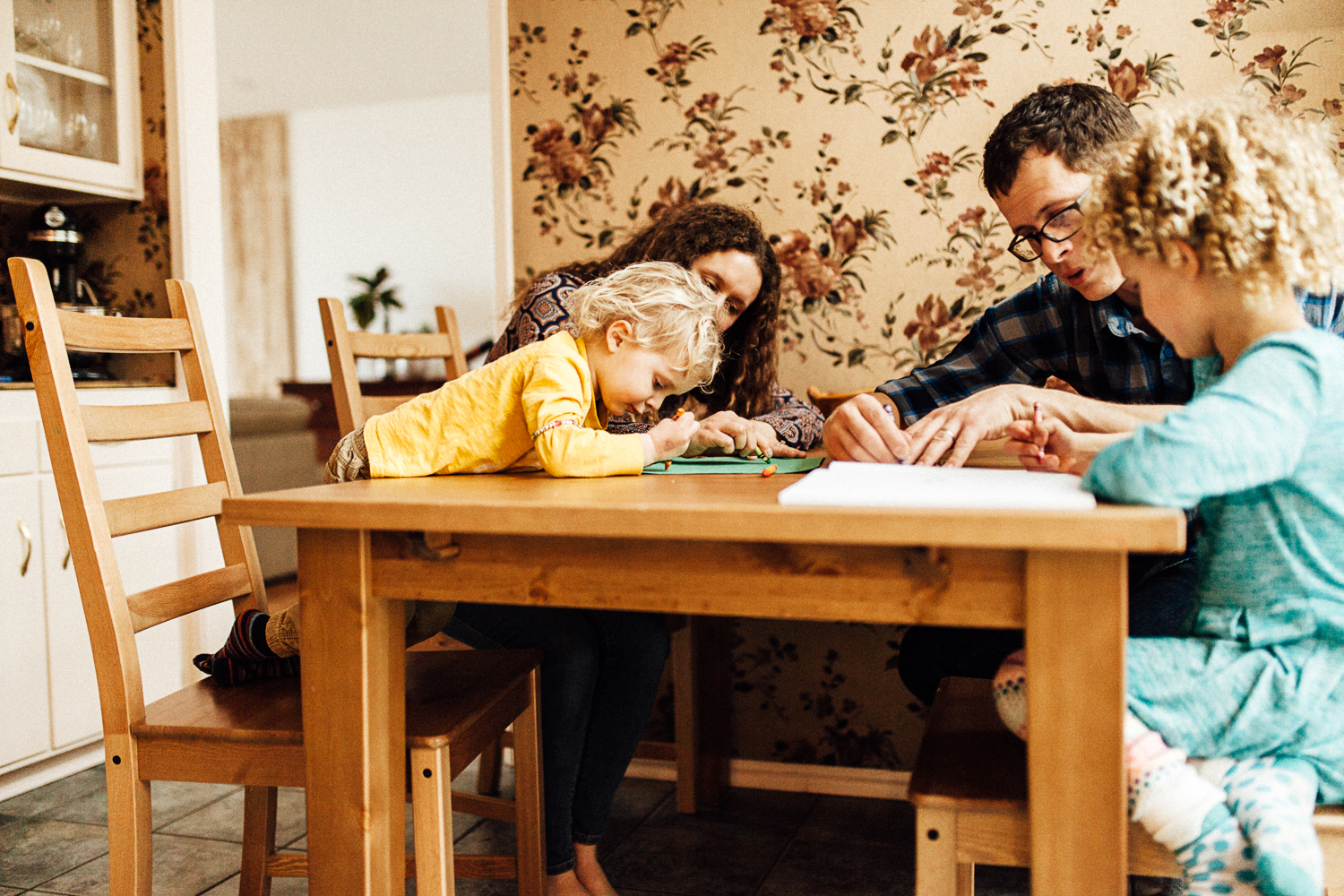family-coloring-at-kitchen-table-during-in-home-photoshoot-millcreek-utah
