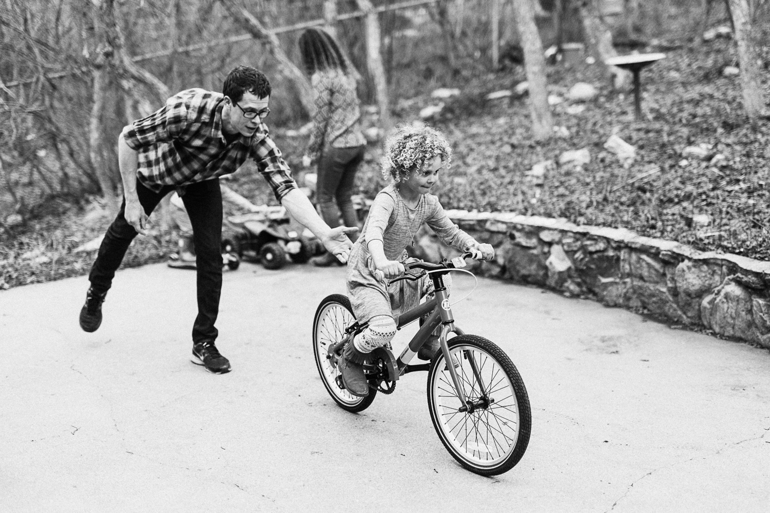 dad-helping-daughter-ride-bike-on-back-porch-at-home-lifestyle-photography-session-with-jen-fairchild-millcreek-utah