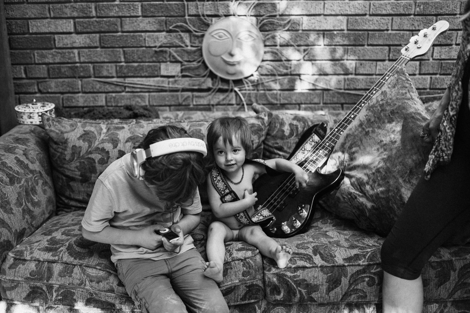 brothers-playing-with-guitar-on-couch-in-backyard-in-home-family-session-with-jen-fairchild-photography-in-sugarhouse-utah