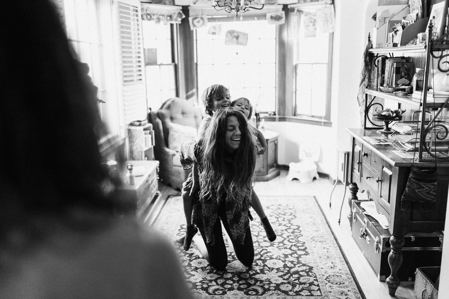 mother-giving-piggy-back-ride-to-children-in-home-family-photo-sessions-with-jen-fairchild-photography-salt-lake-city-utah