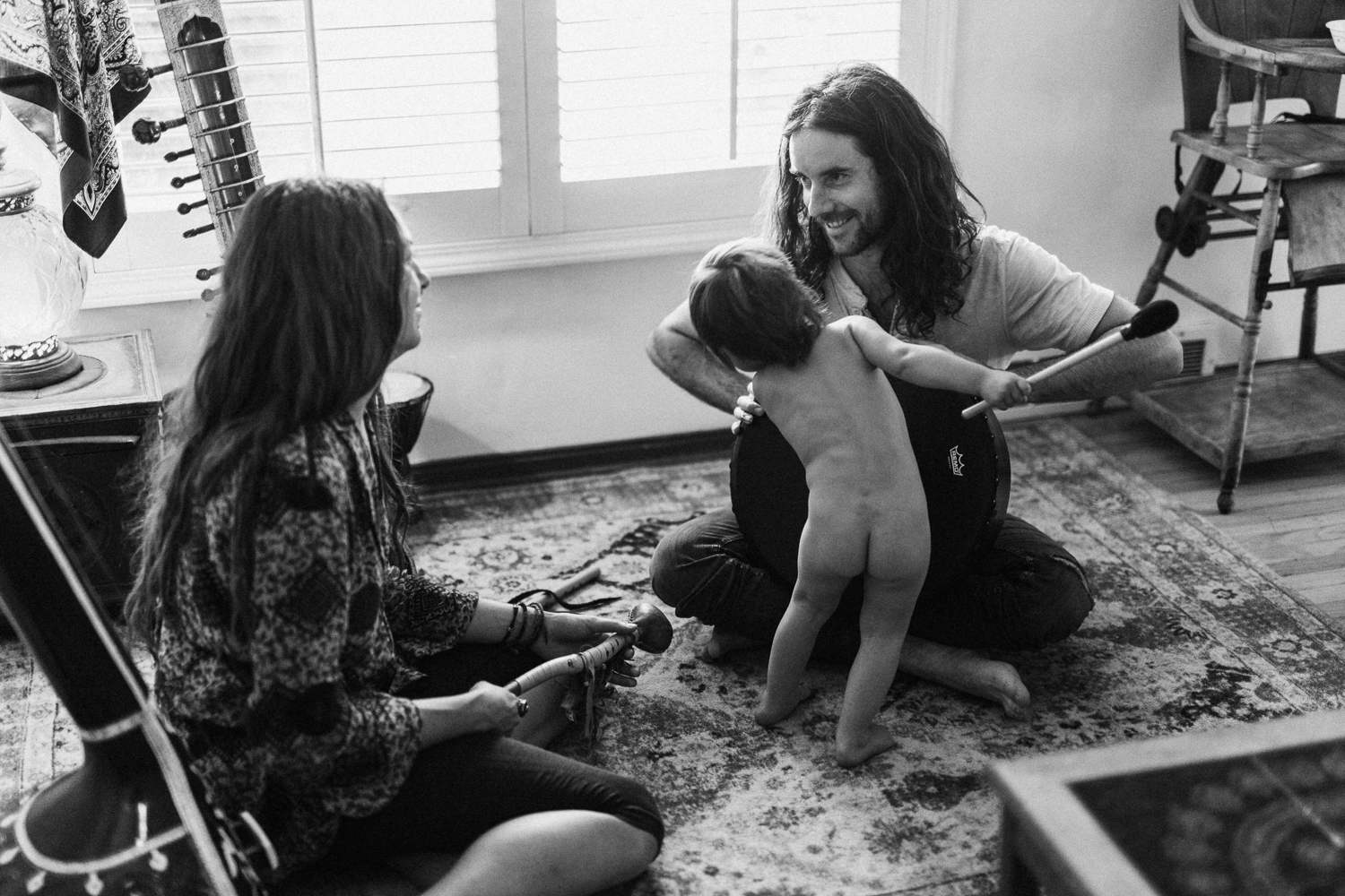father-playing-with-child-while-gazing-at-mother-during-in-home-family-photo-session-with-jen-fairchild-photography-sugarhouse-slc-utah