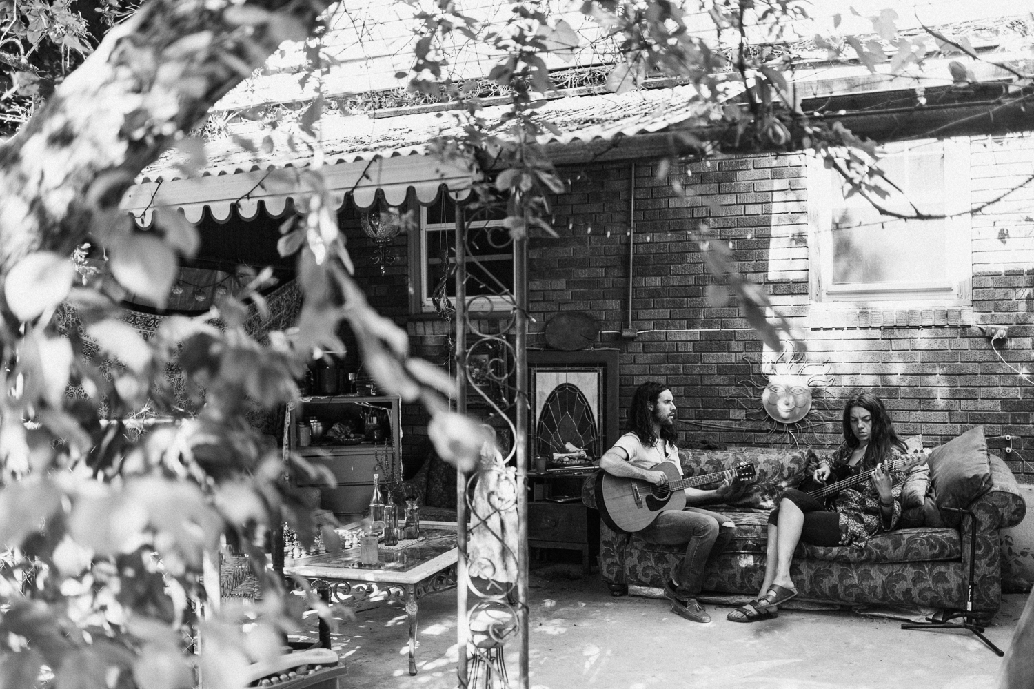 husband-and-wife-jamming-on-couch-in-backyard-family-photo-session-with-jen-fairchild-photography-slc-ut