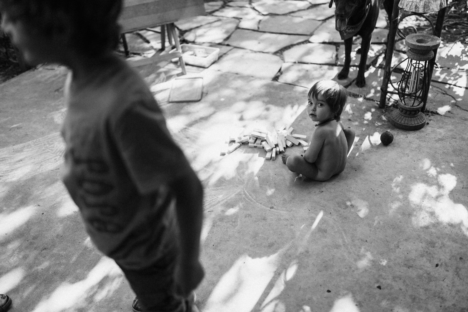 black-and-white-photo-young-girl-playing-on-cement-in-backyard-family-photo-sessions-with-jen-fairchild-photography-slc-ut