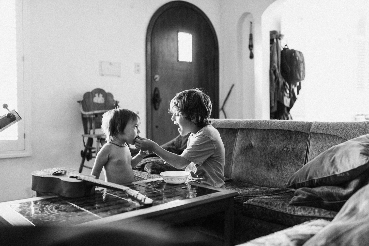 brother-feeding-little-sister-black-and-white-in-home-family-photo-session-with-jen-fairchild-photography-sugarhouse-utah
