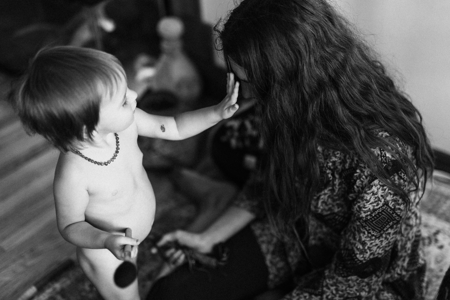 baby-shaman-touching-mothers-third-eye-black-and-white-in-home-family-photo-session-with-jen-fairchild-photography-in-salt-lake-city-sugarhouse-ut