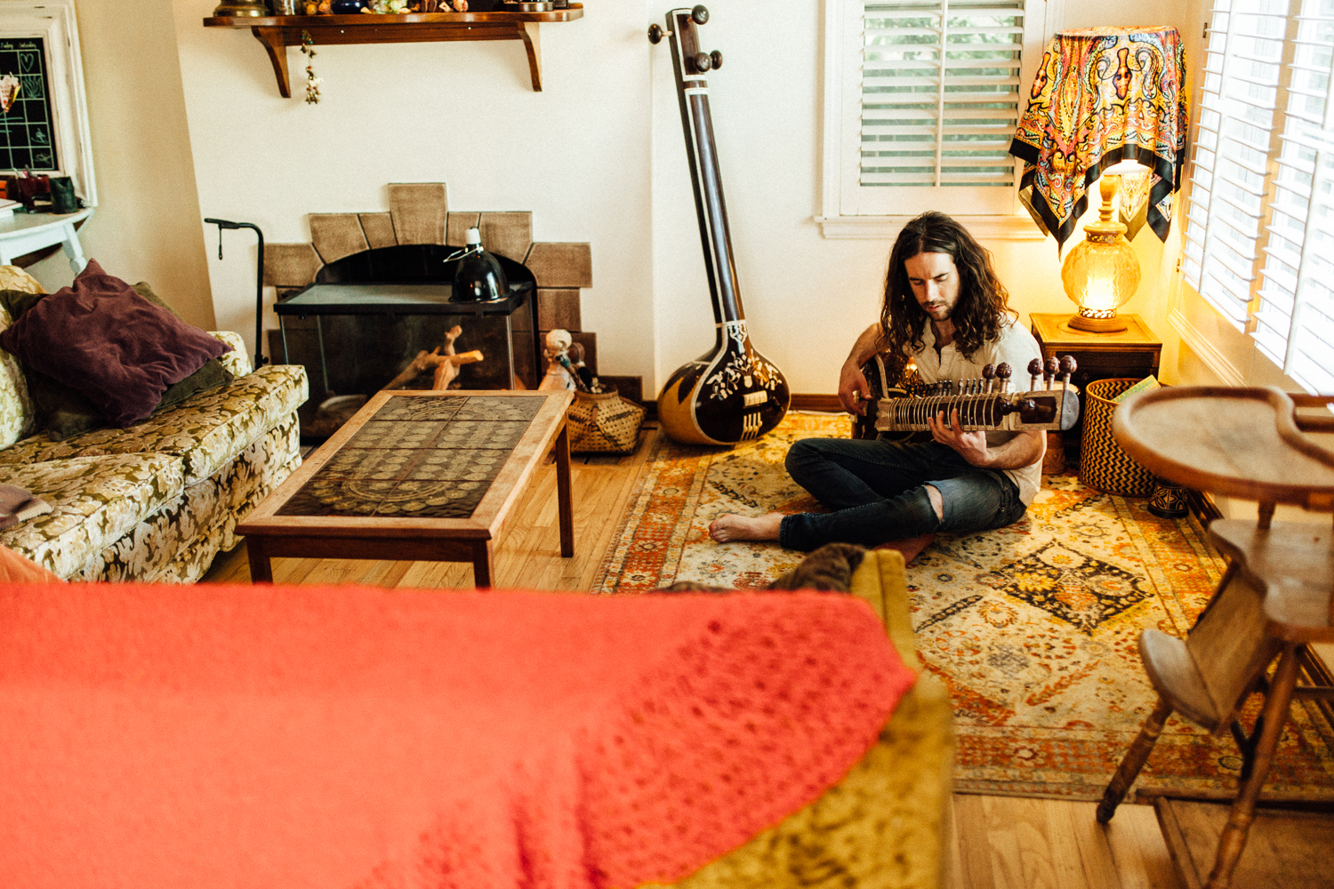 man-sitting-on-floor-playing-musical-instrument-photo-session-with-jen-fairchild-photography-slc-utah