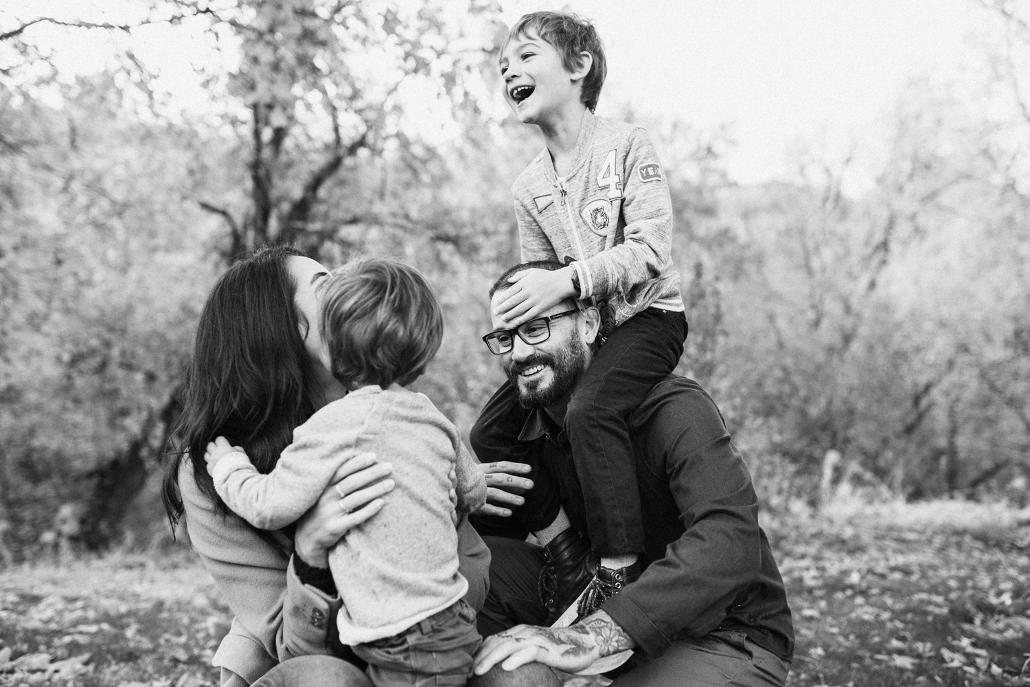 black-and-white-candid-family-photo-playing-in-fall-leaves-during-free-family-portrait-on-location-with-jen-fairchild-photography-in-slc-ut