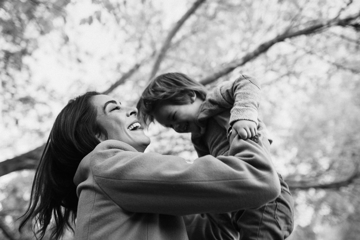 black-and-white-candid-photo-of-mother-playing-with-son-in-fall-leaves-during-free-family-portrait-session-with-jen-fairchild-photography-in-slc-ut