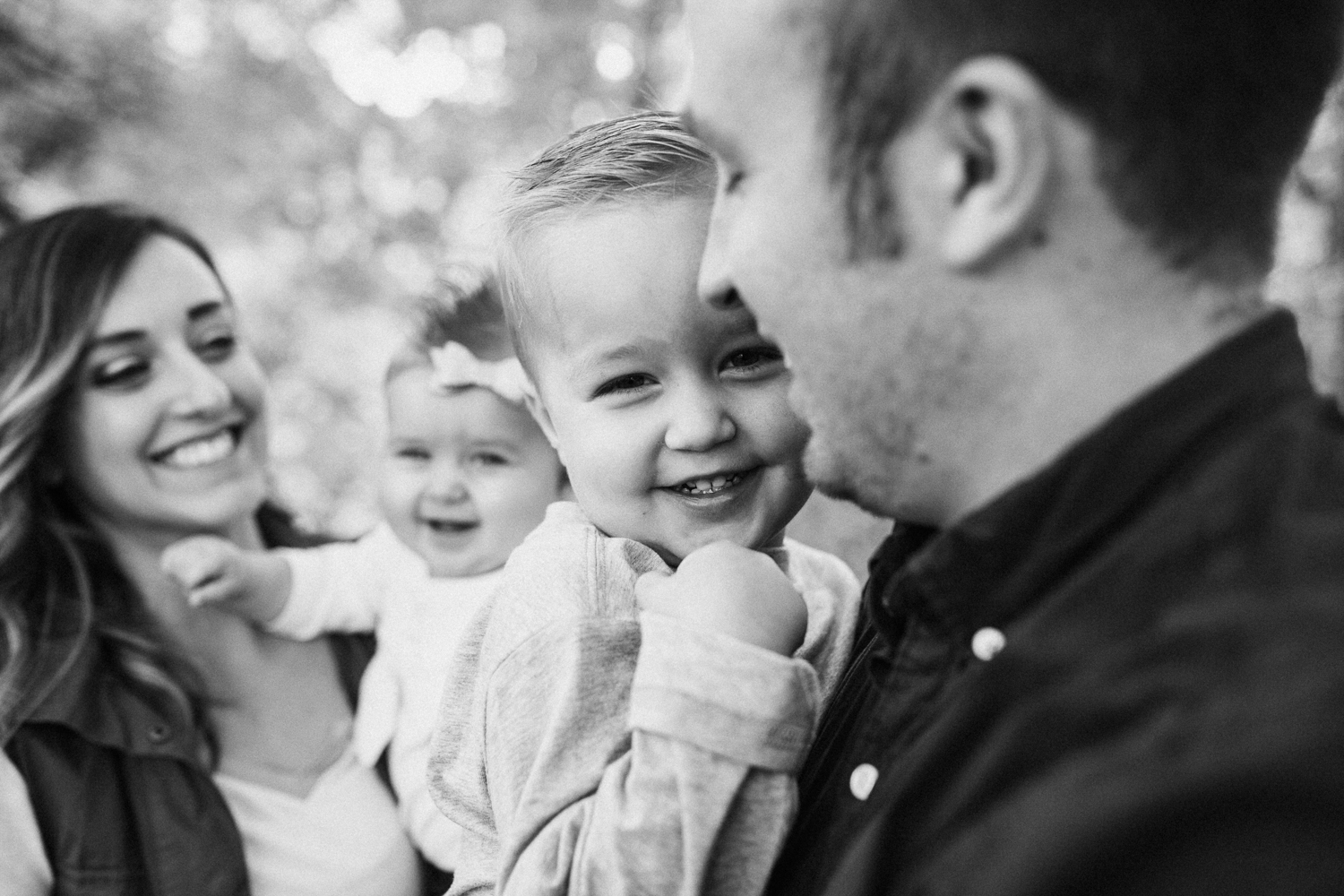 black-and-white-photo-of-parents-holding-children-during-free-family-session-with-jen-fairchild-photography-at-rotary-glenn-park-in-slc-ut