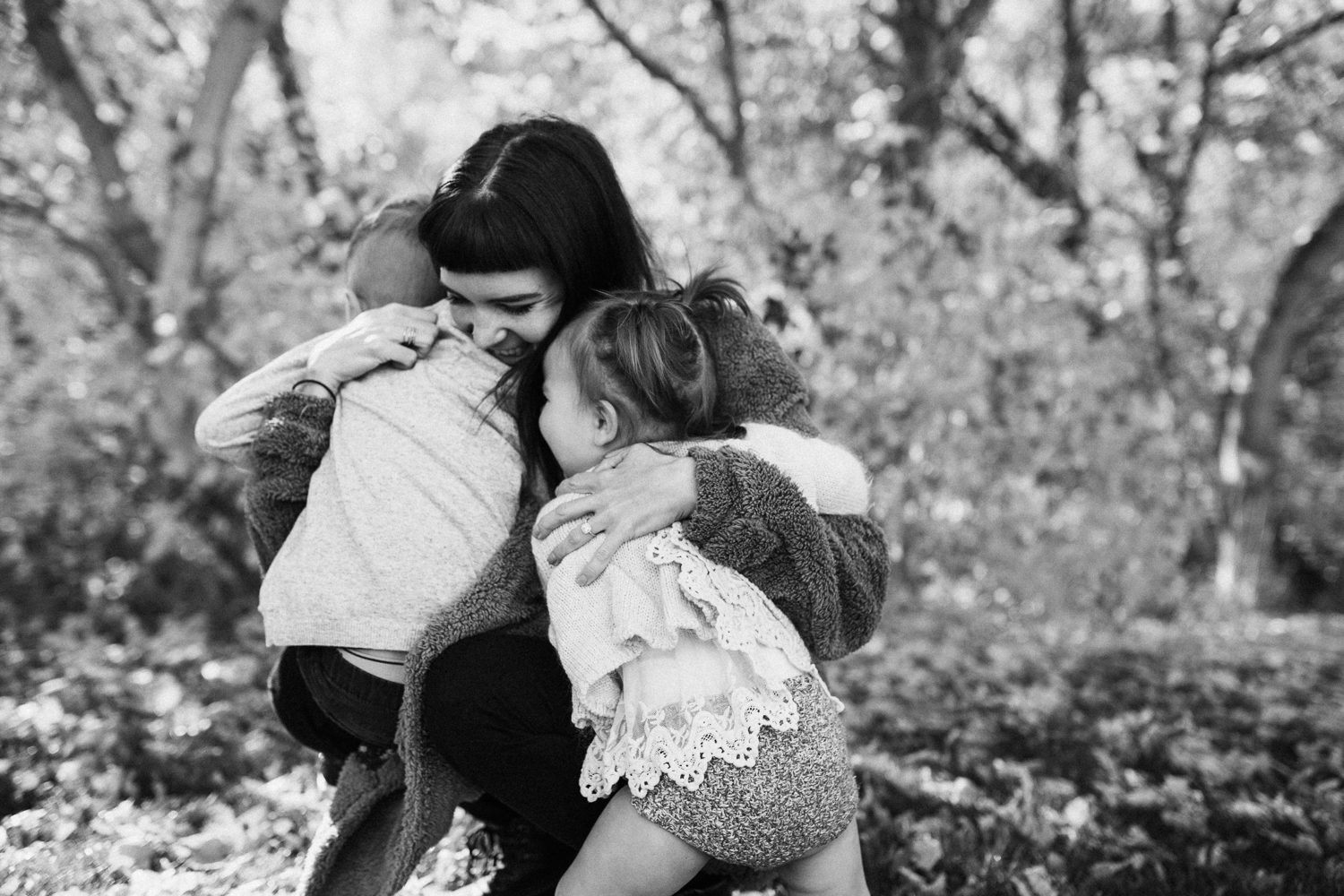 candid-black-and-white-of-children-hugging-mother-at-park-during-free-family-mini-session-with-jen-fairchild-photography-in-salt-lake-city-utah