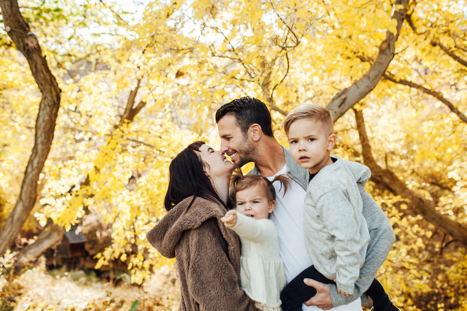 candid-family-photo-in-fall-leaves-during-free-family-mini-session-with-jen-fairchild-photography-salt-lake-ut